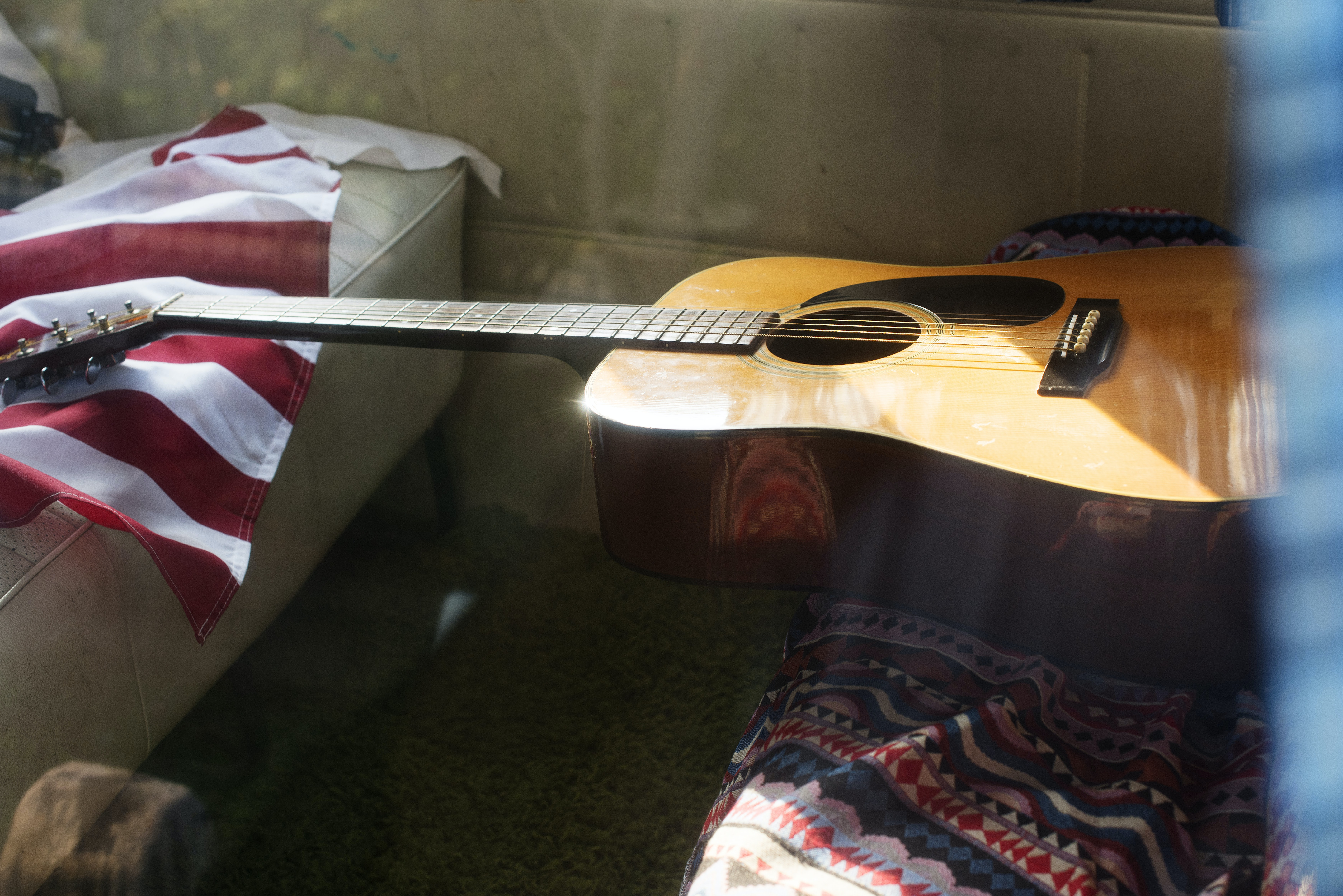brown acoustic guitar near white leather padded sofa
