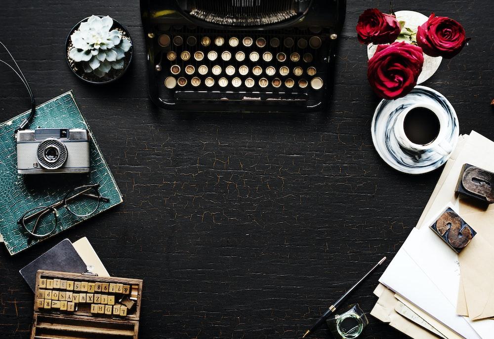 black typewriter on black wooden-top table