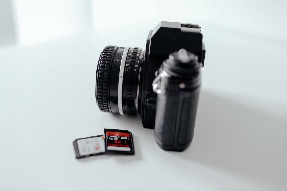 two black memory cards beside black DSLR camera on white surface