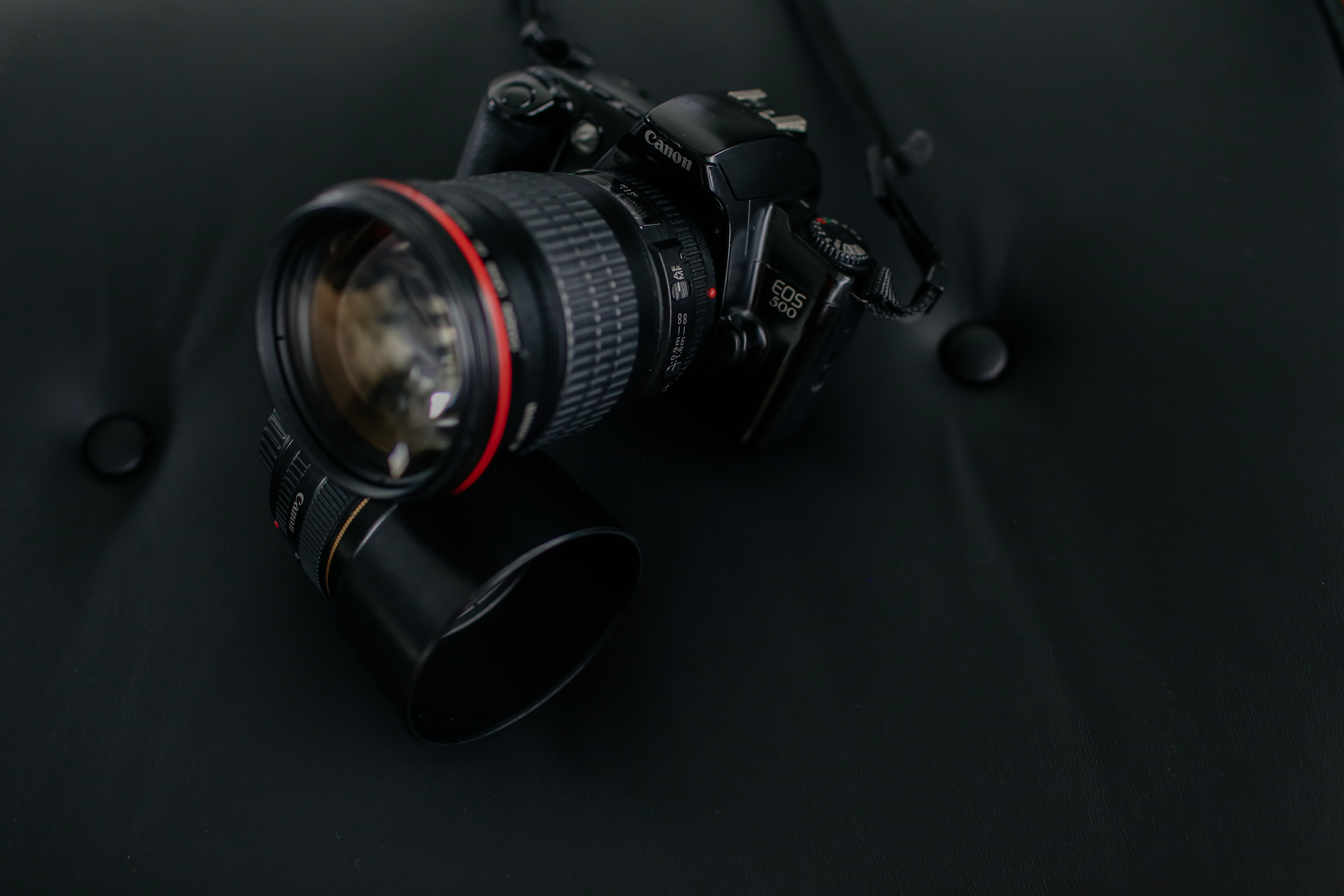 Canon EOS camera with lens on black seat