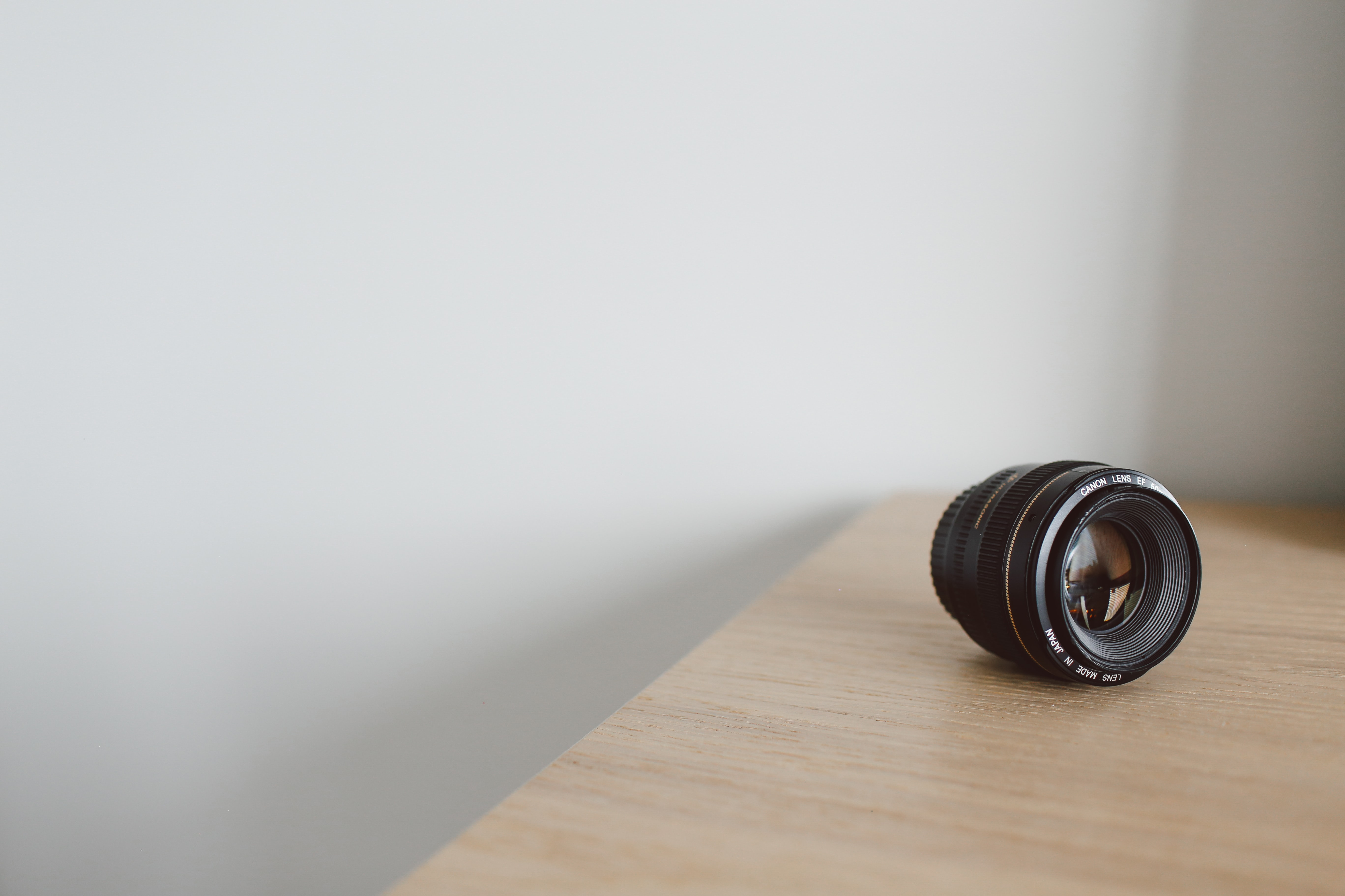 A Canon camera lens on a wooden surface near a white wall