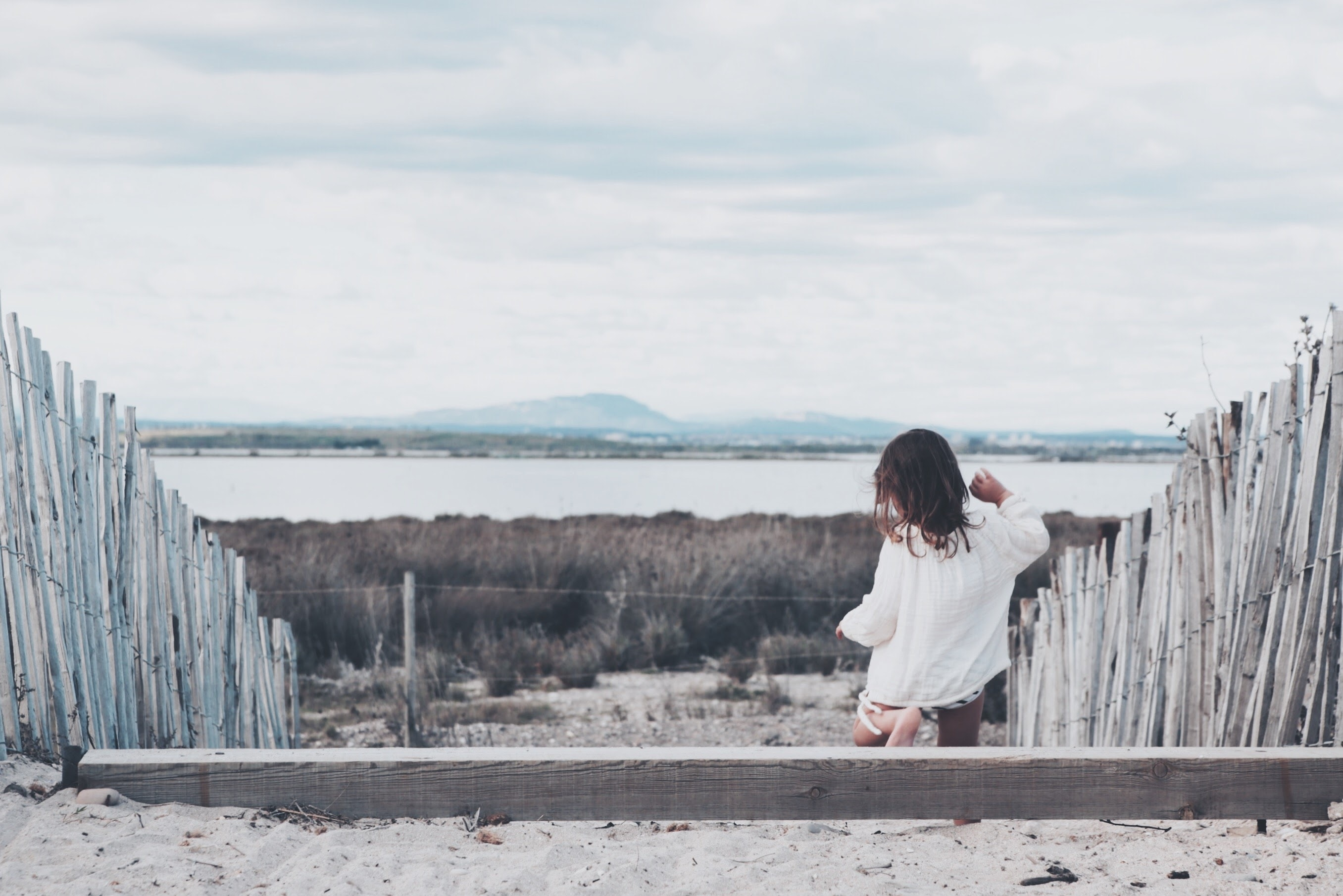 girl stepping down on wooden steps with wooden fence towards brown grassfield