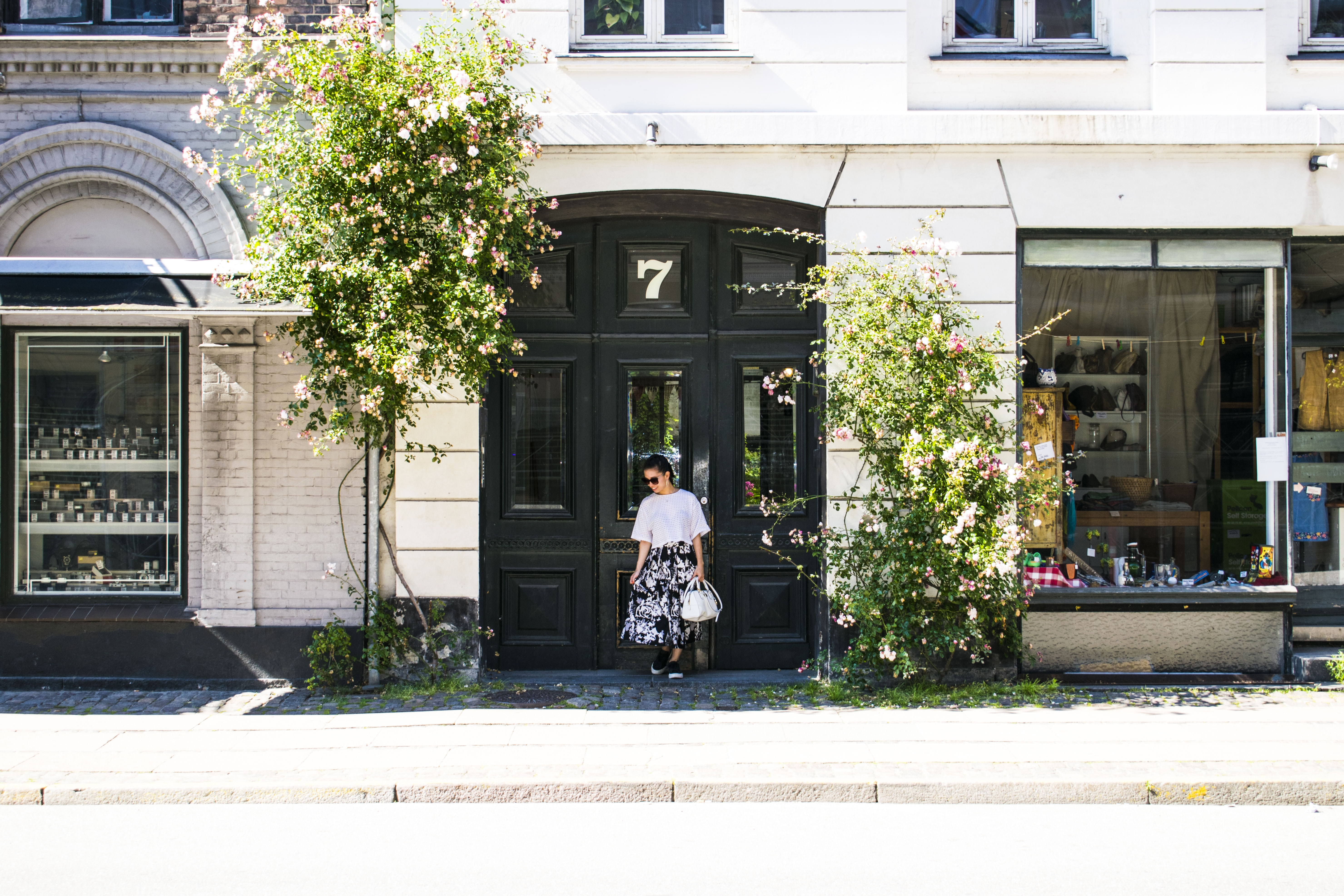 woman carrying bag white standing in front of door during daytime