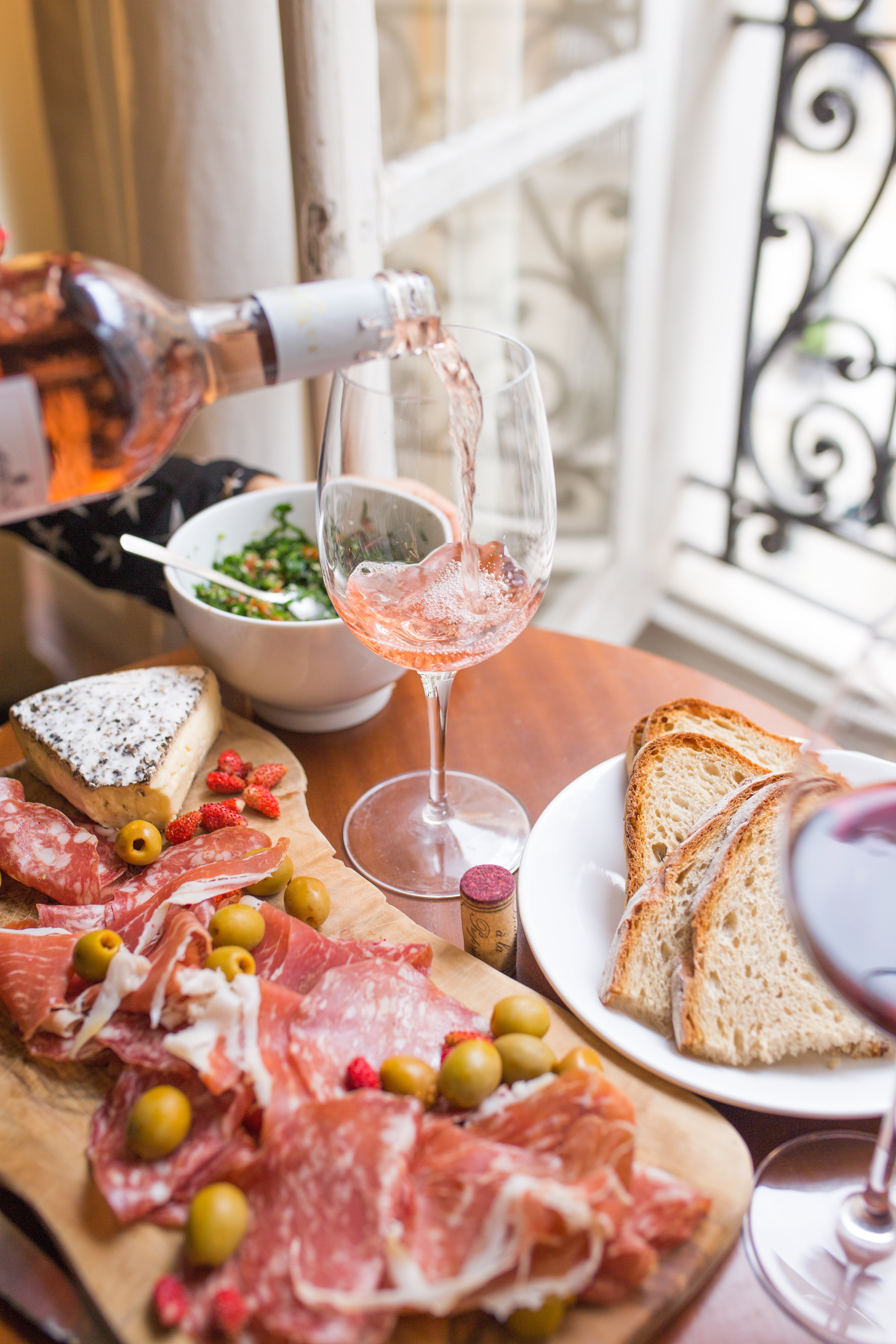 A person pouring rose into a wine glass, a cheese board with brie and salami, and bread on a table in Paris