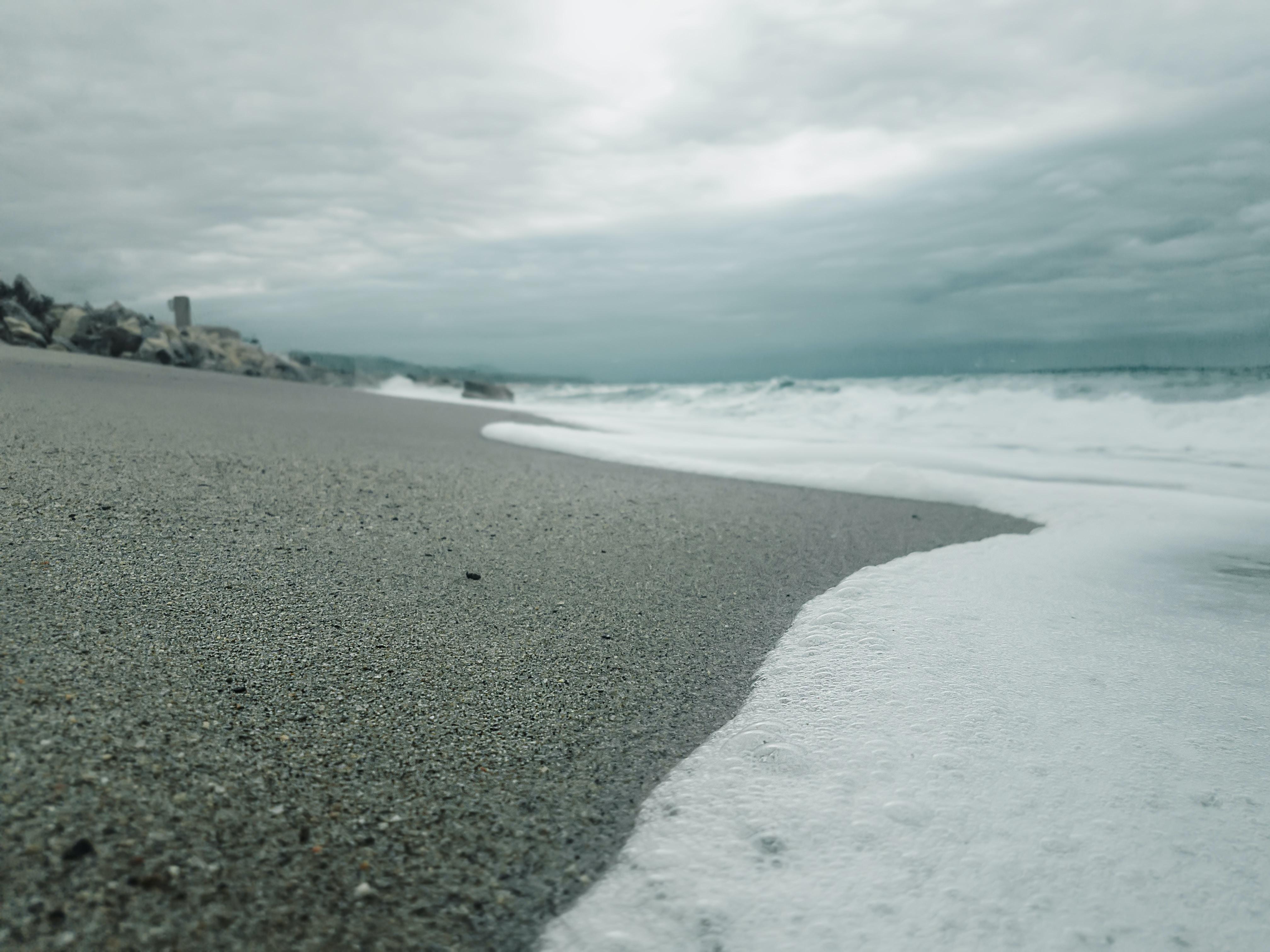 Ocean foam washing on a fine dark sand beach