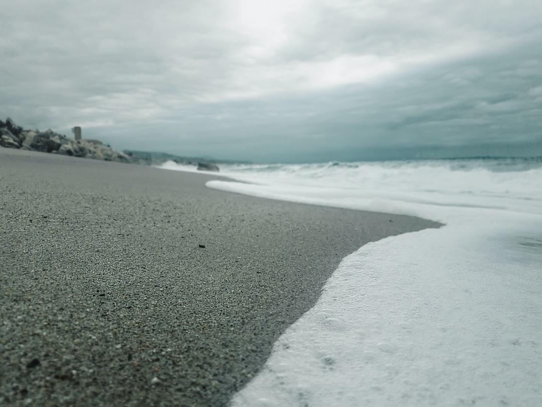 Ocean foam on dark sand beach