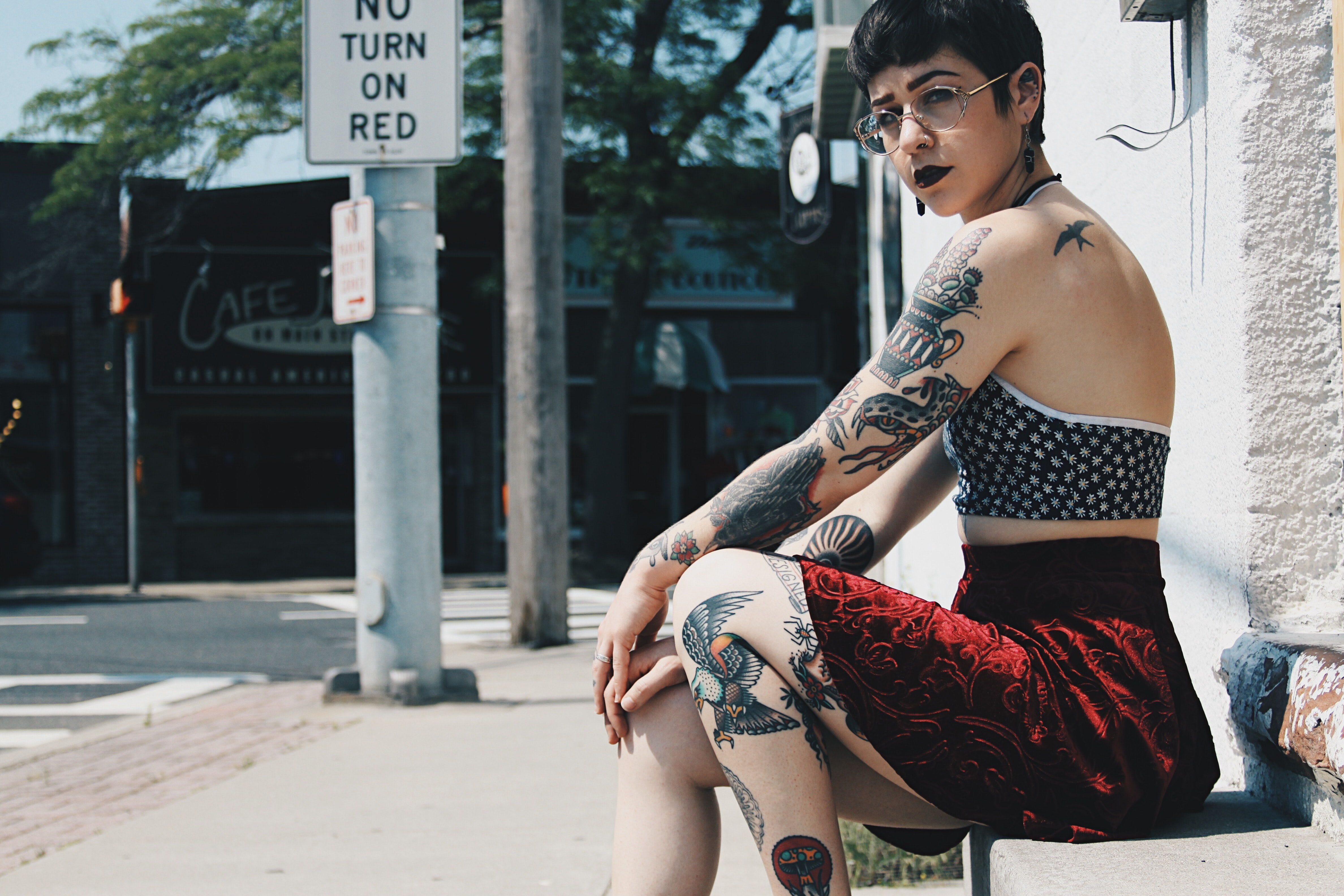 Woman with edgy tattoos wearing a skirt sits on a bench outside