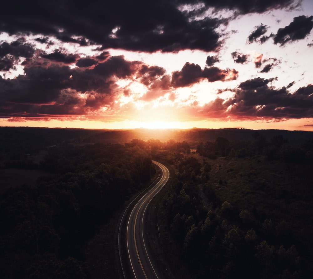 aerial view of a road surrounded by trees during sunset