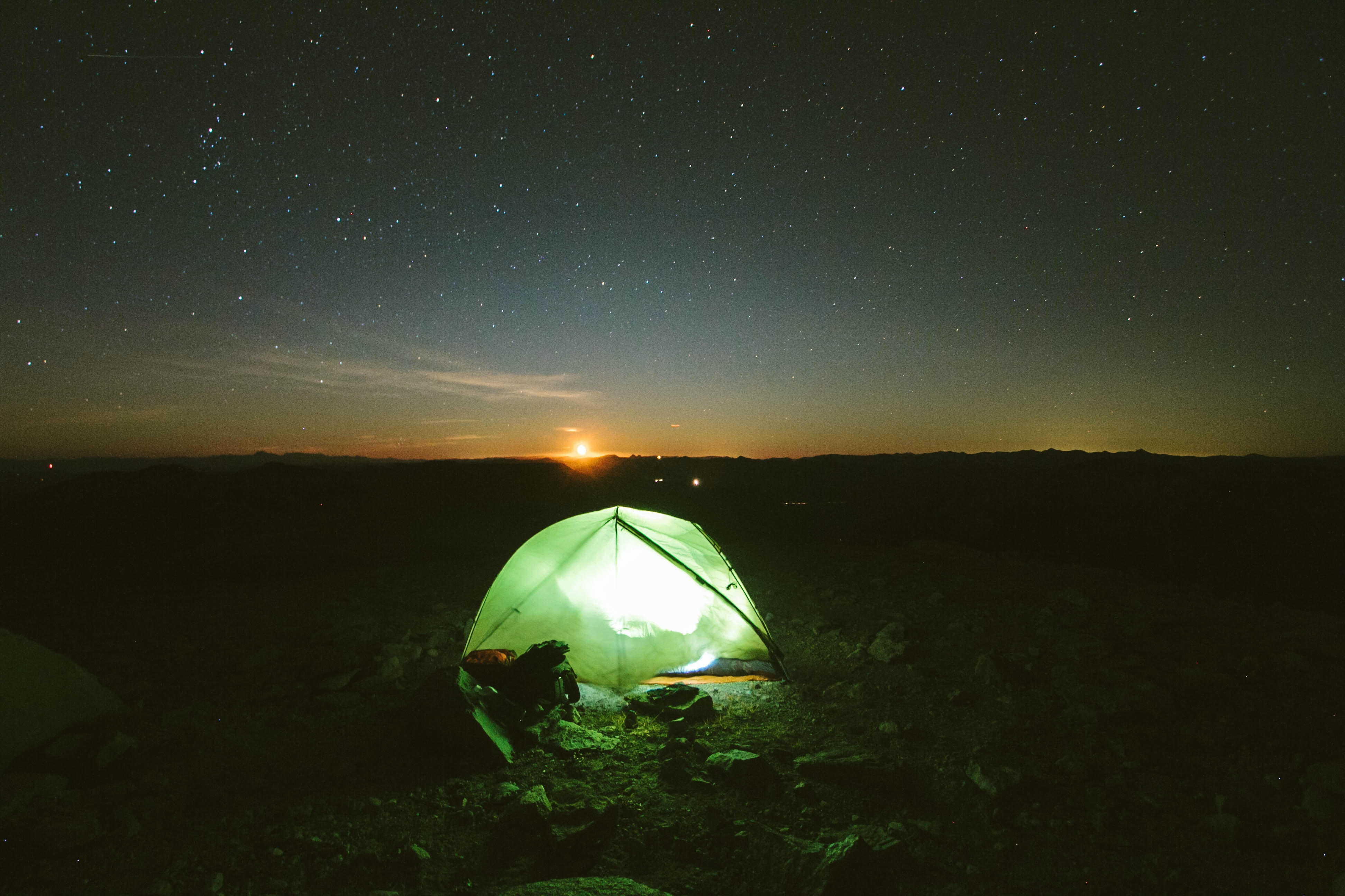 A lighted tent under the night sky with the sun on the horizon.