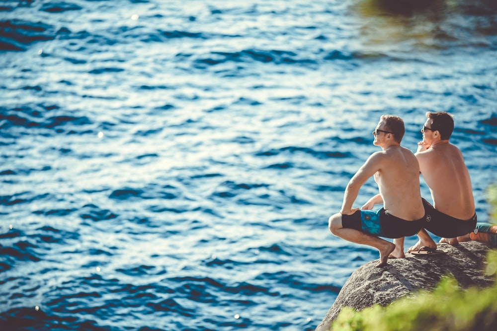 two men sitting on cliff in front of body of water