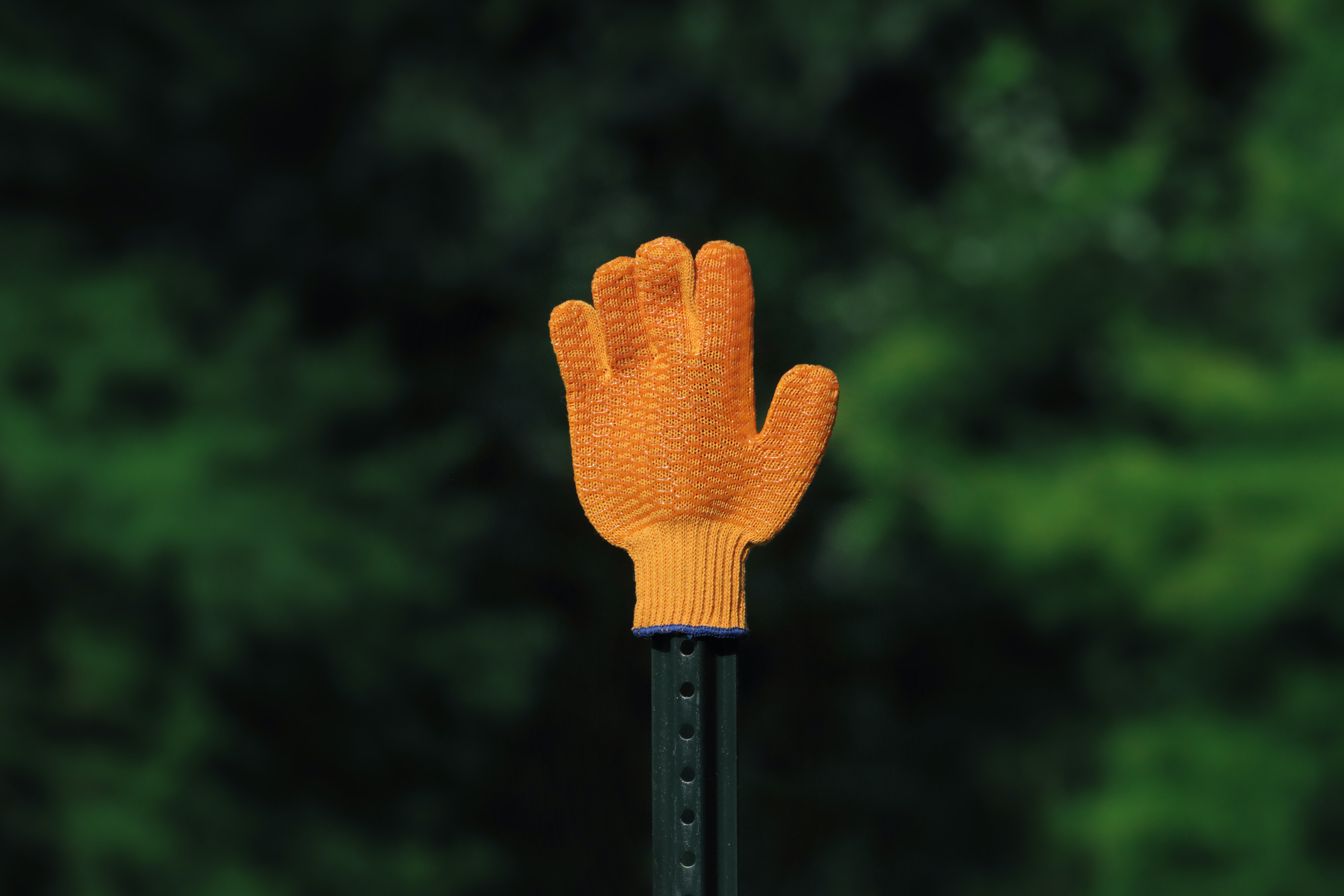 A child-sized orange-colored glove on a sign post