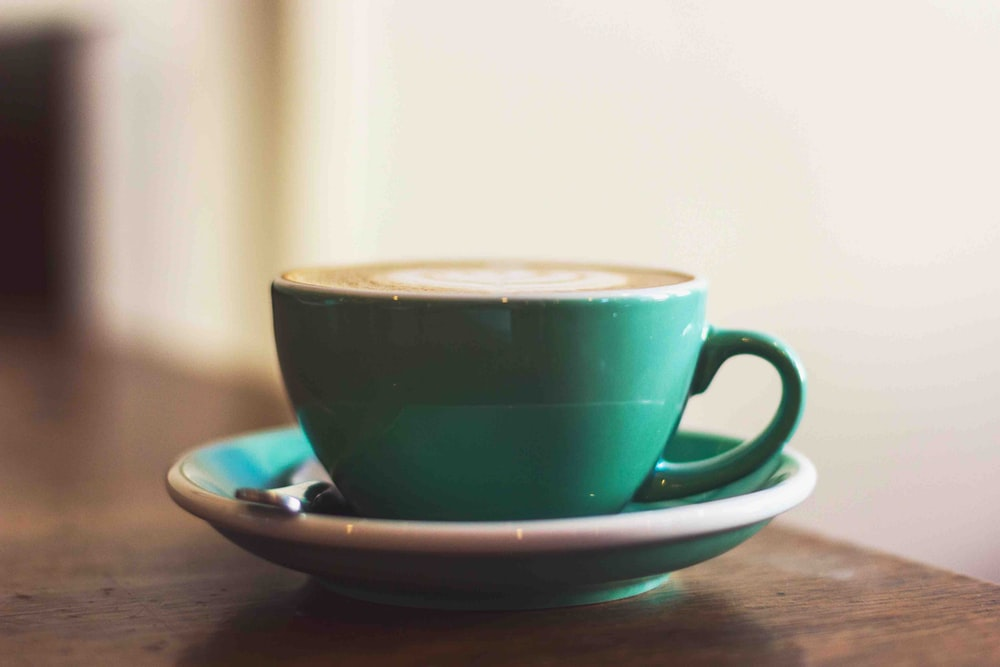 selective focus photography of cup of coffee on green saucer