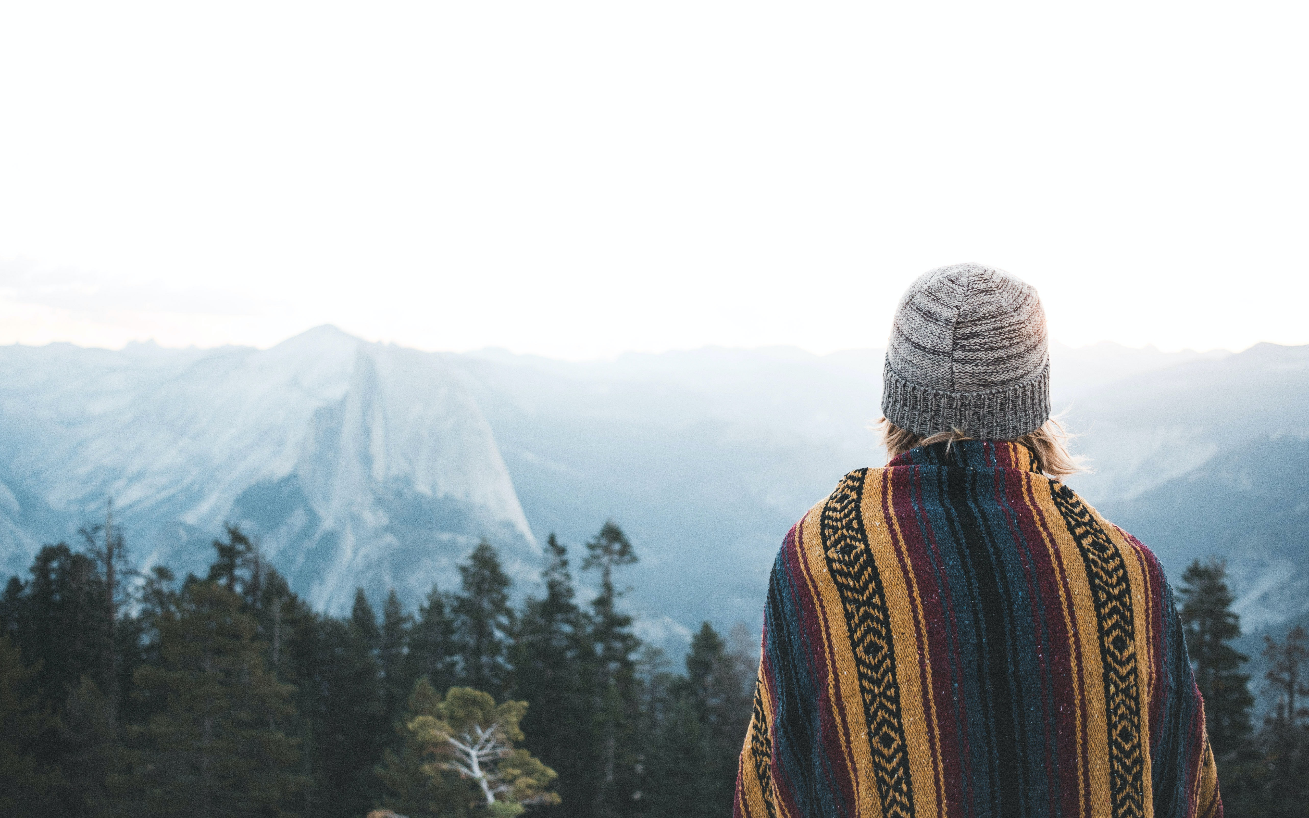 A woman in a knit cap looking off on the distant cliffs in Yosemite Valley