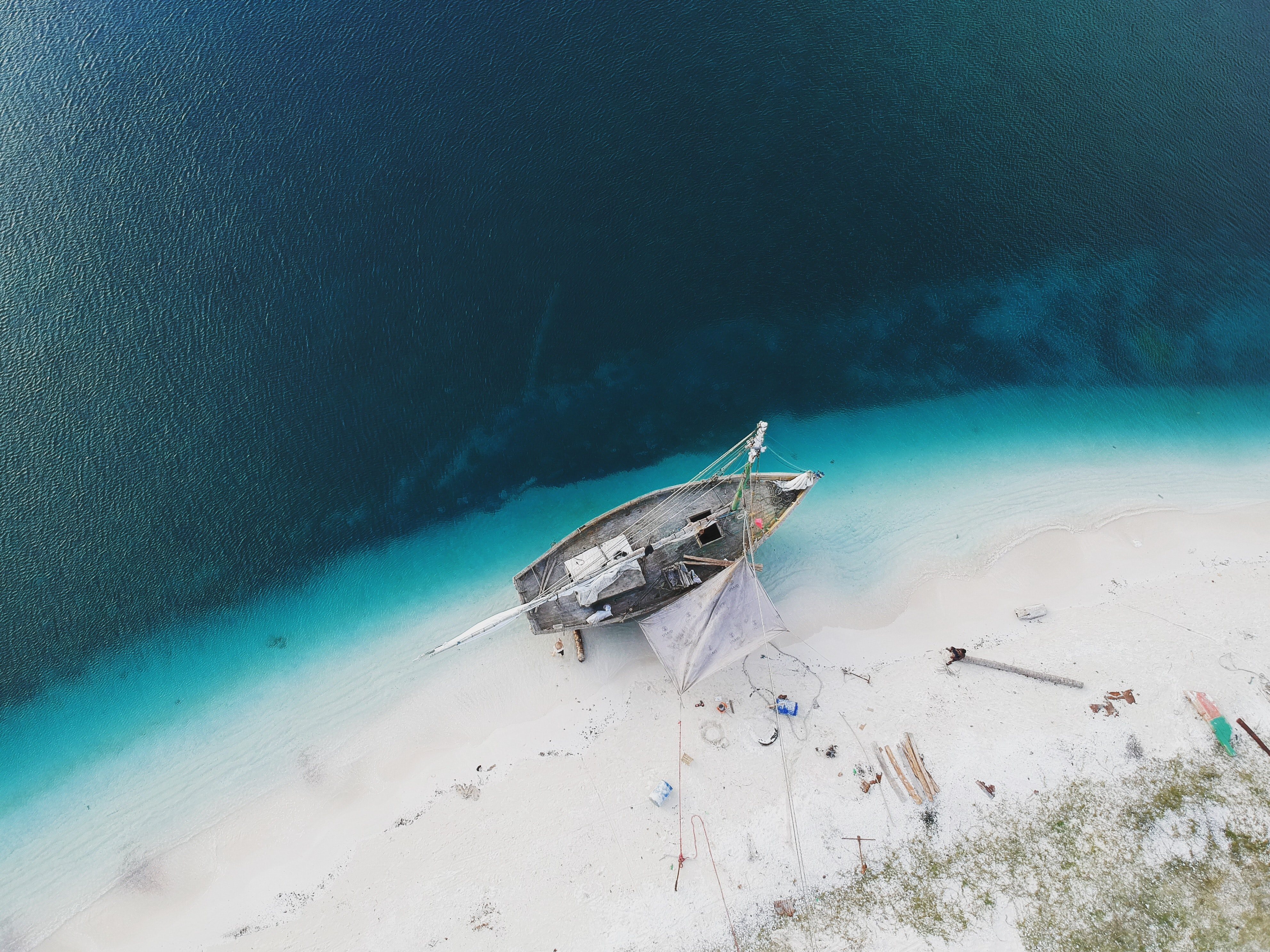 Drone aerial view of the boat being repaired on the sand beach in Pointe Figuier, Sud Department, Haiti