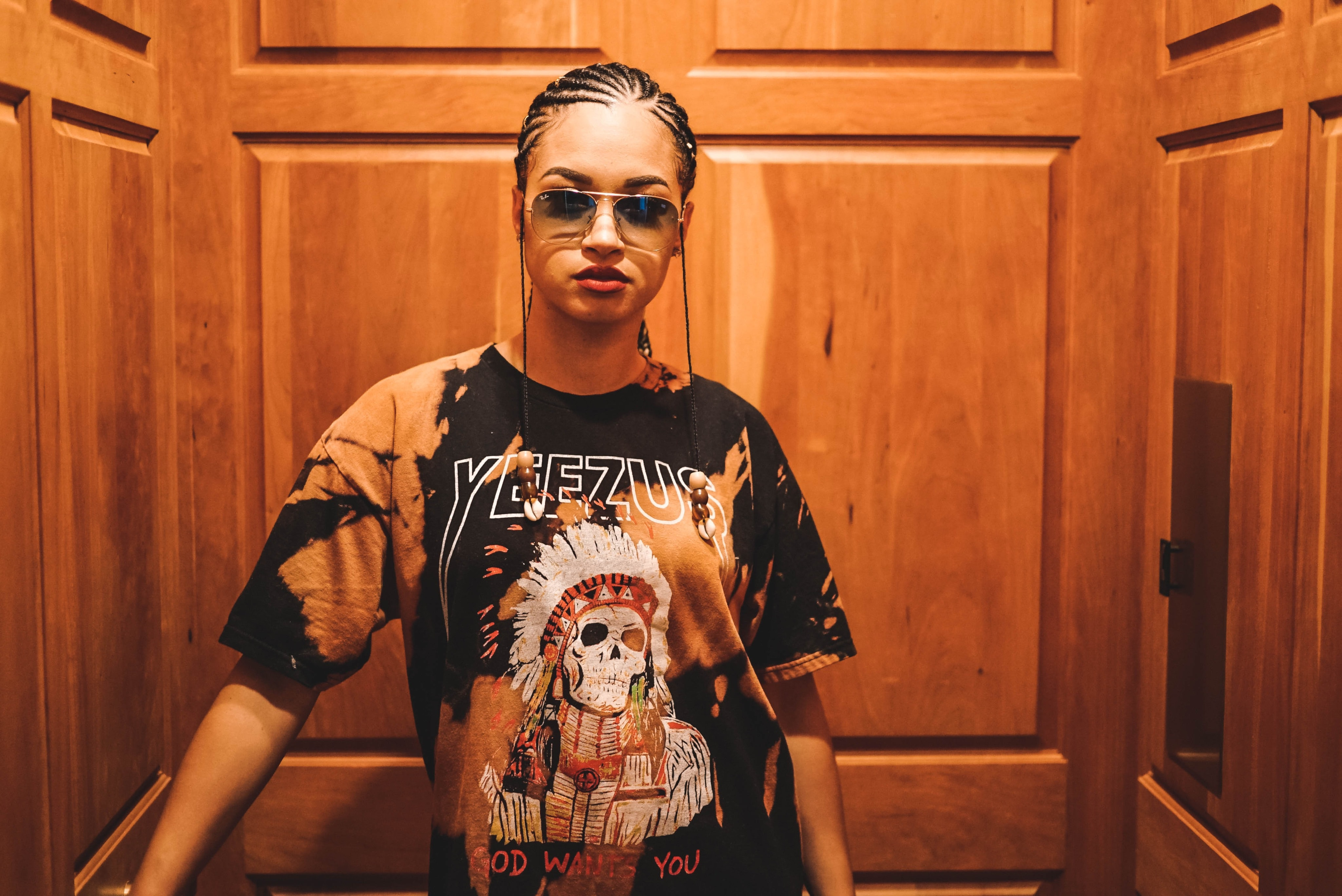 Trendy woman with cornrow braids and a yeezus t-shirt in an elevator