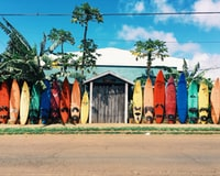 blue and white house surrounded by surfboards during daytime