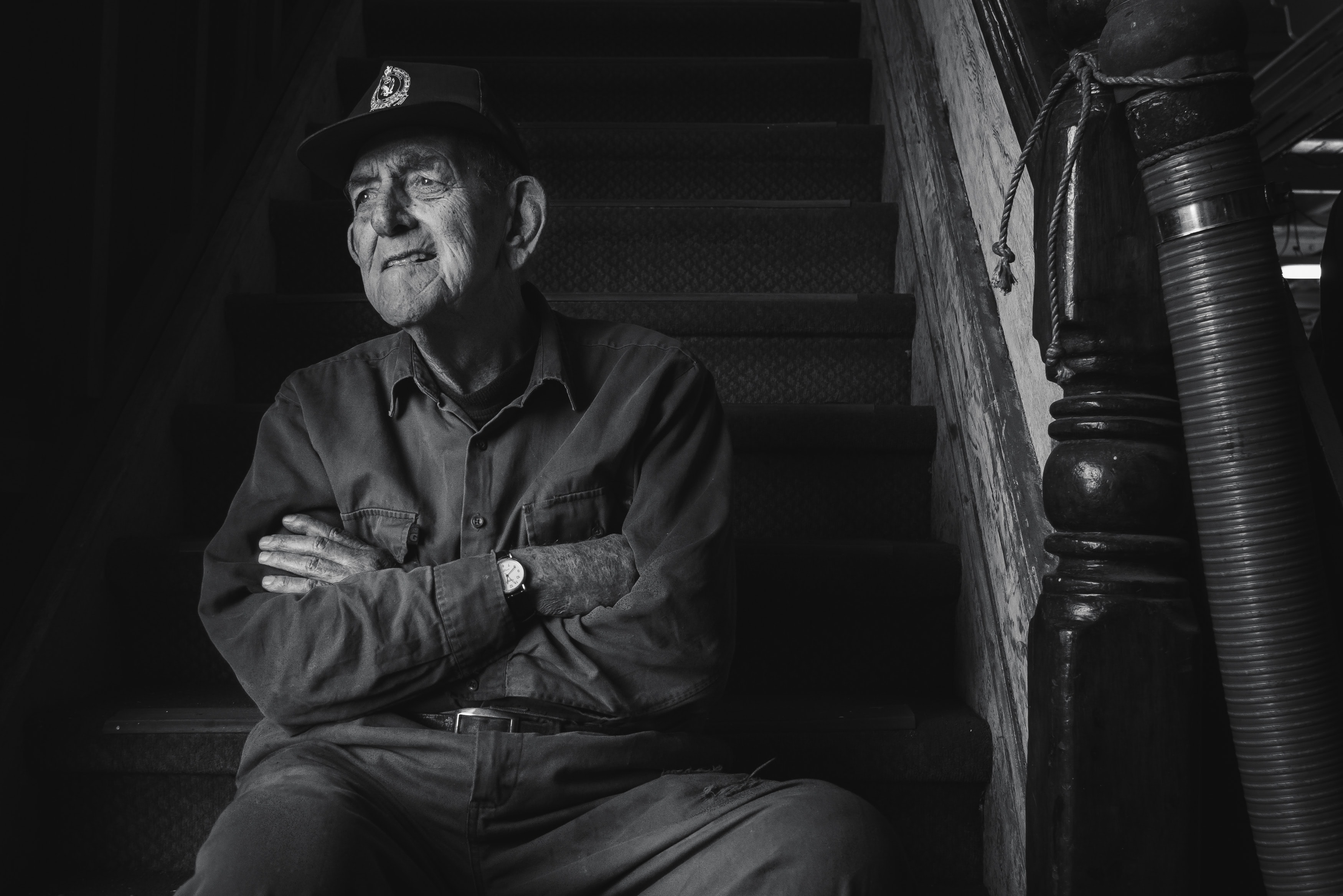 grayscale photo of man sitting on stair