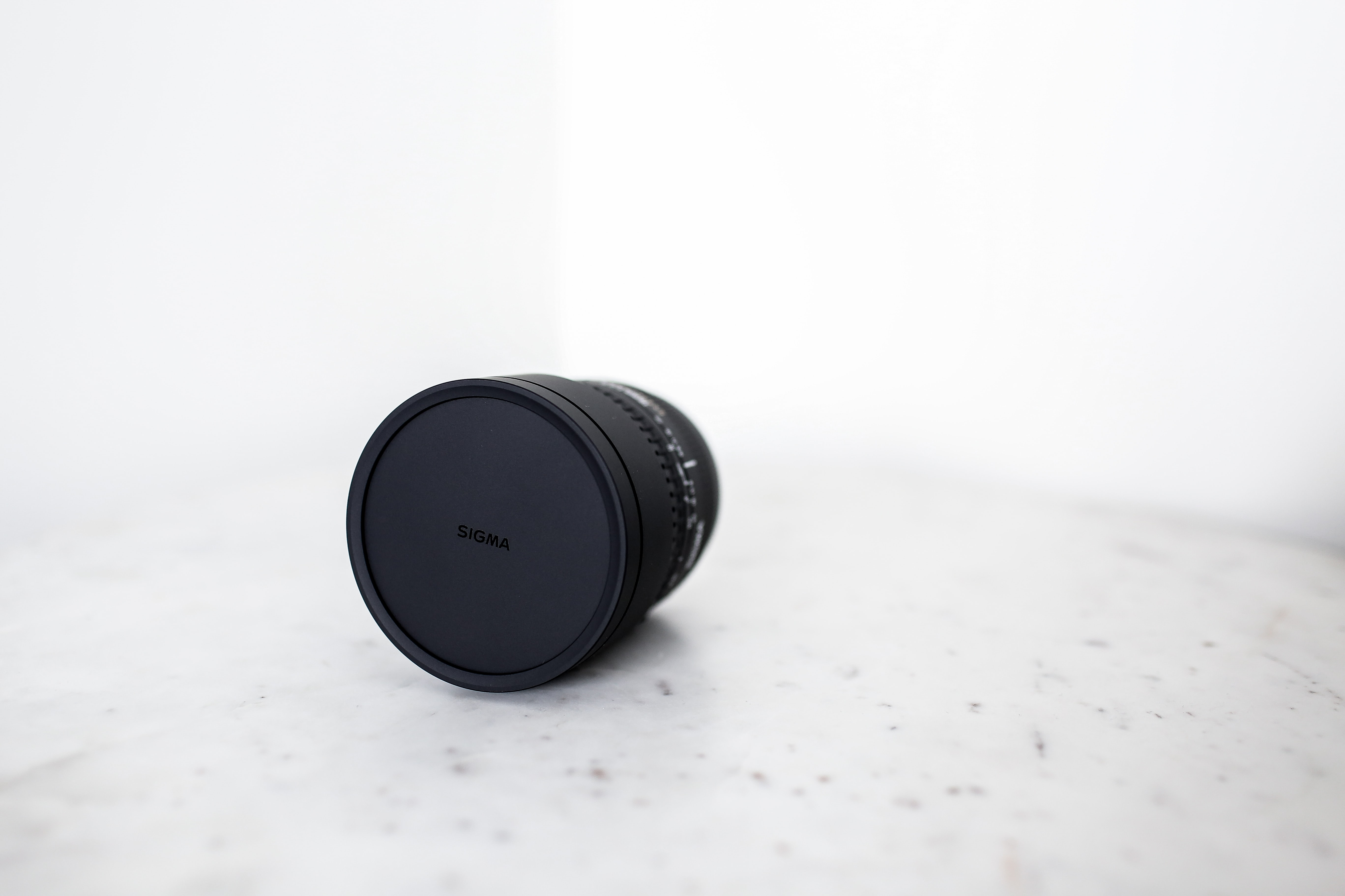 A Sigma lens with its cover on a white marble surface in front of a white wall