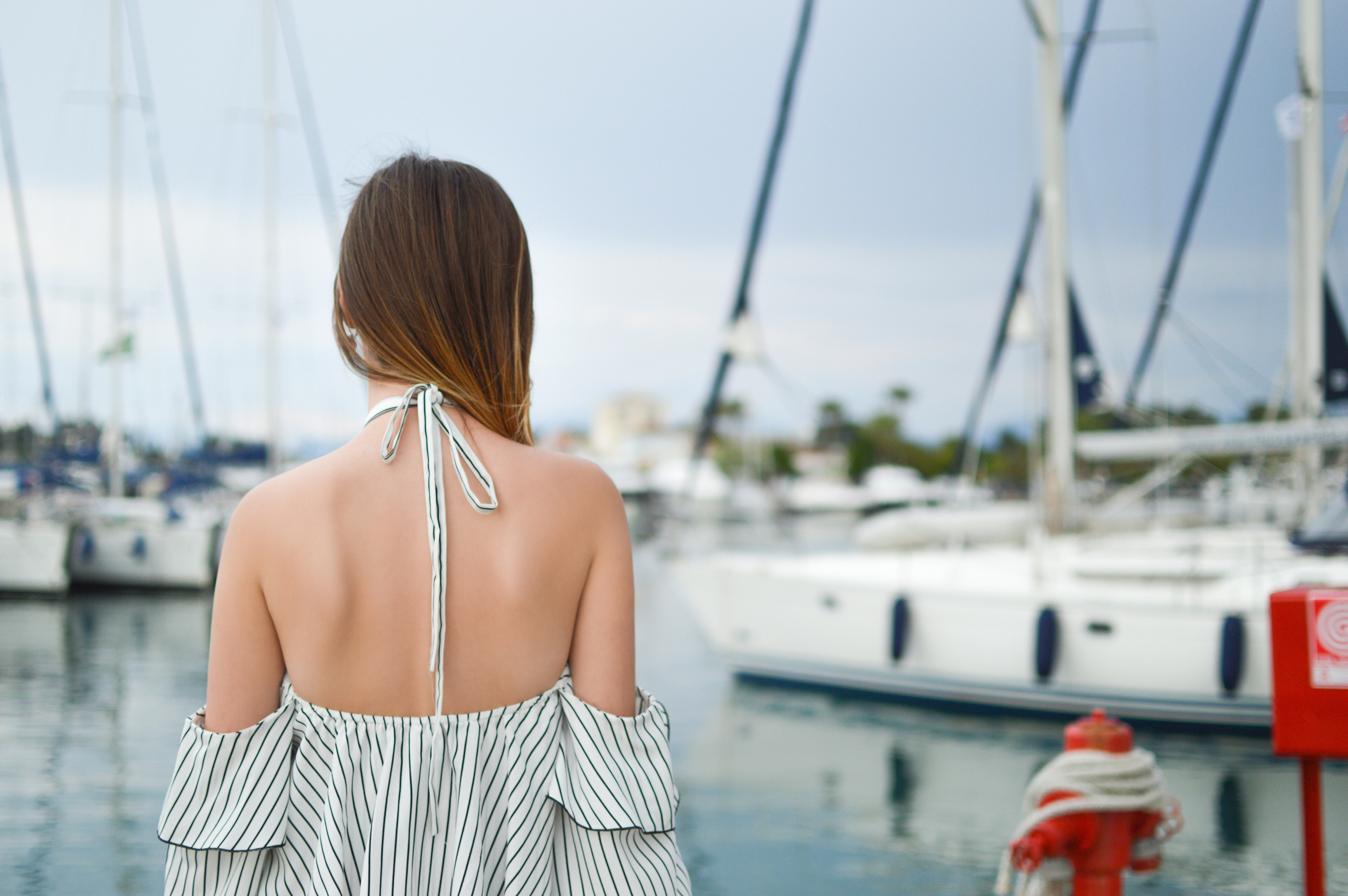 A woman in an off-the-shoulder top looks away from the camera toward boats at Gouvia Marina