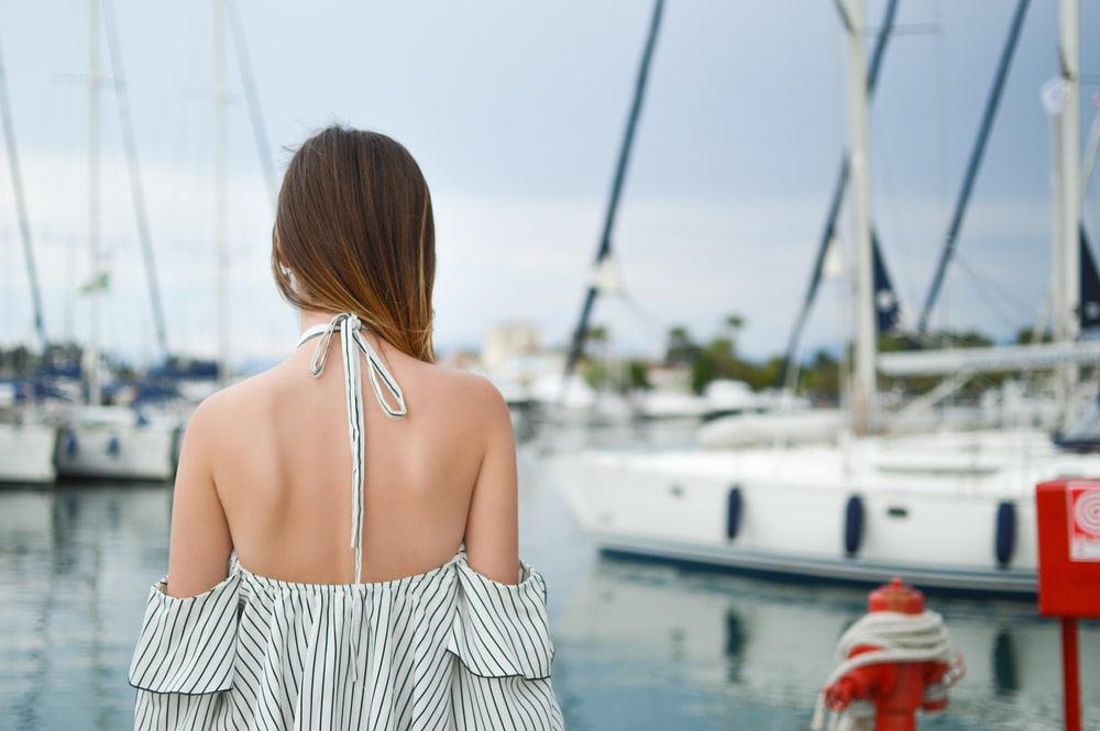 woman in black and white striped cold-shoulder halter top near white yacht