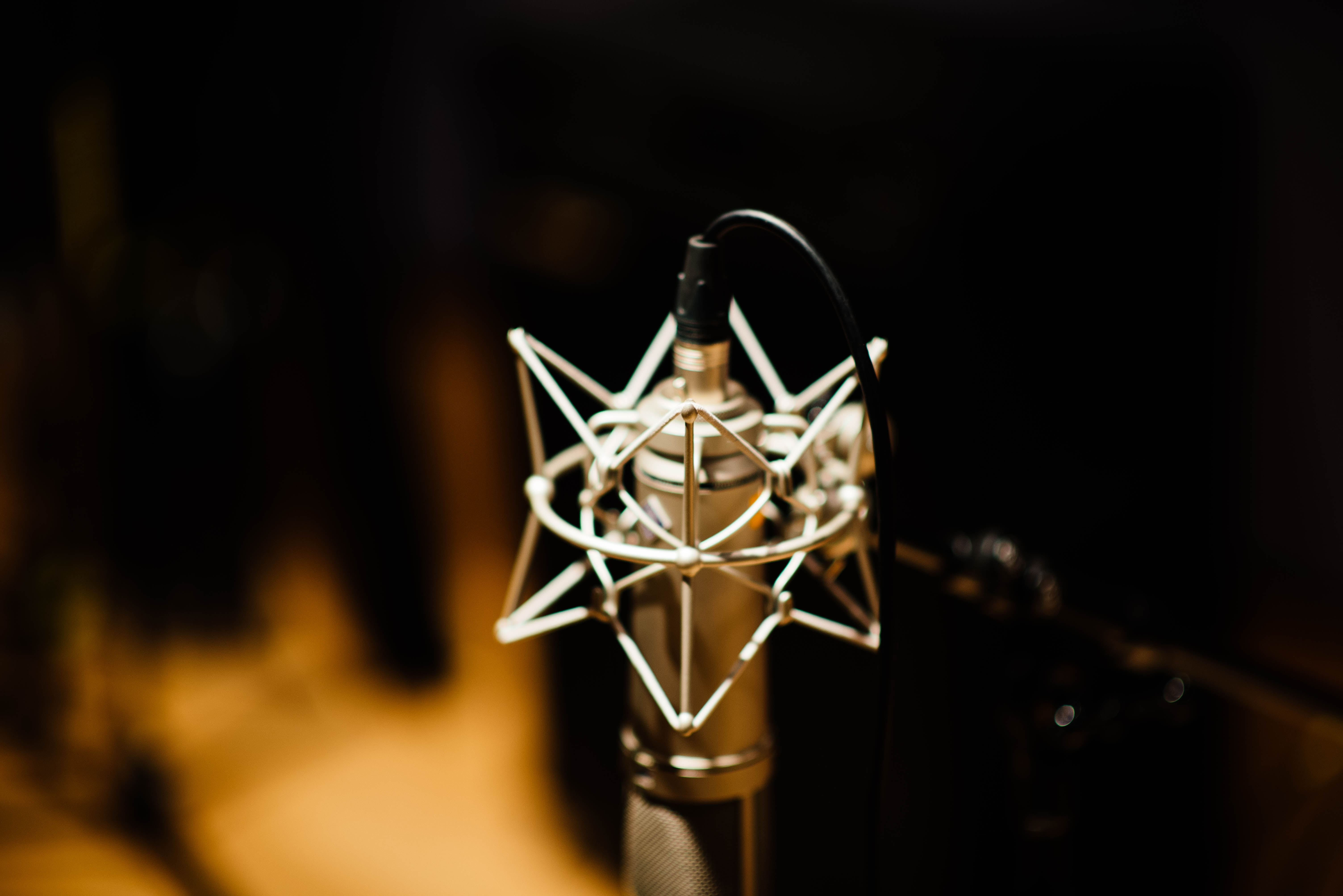 A macro shot of a retro microphone with a blurry dark background