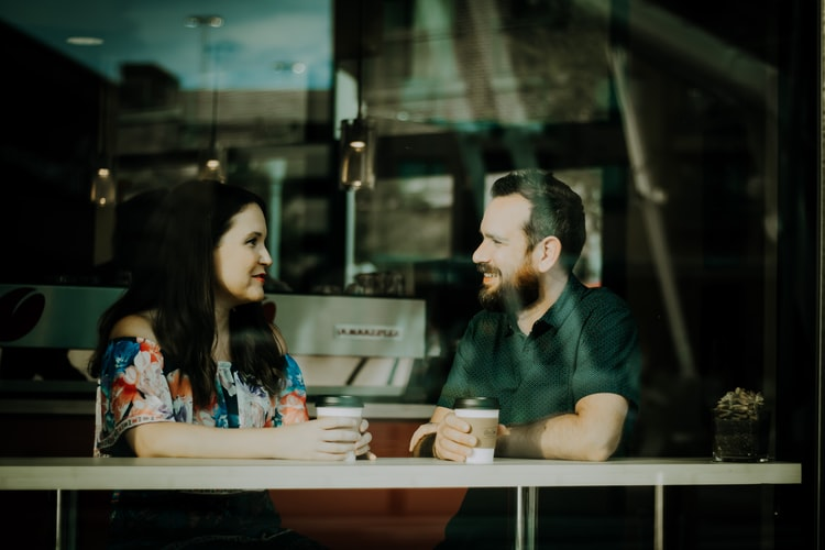 Man and a woman having a conversation in a Bee Cave Coffee Co. shop