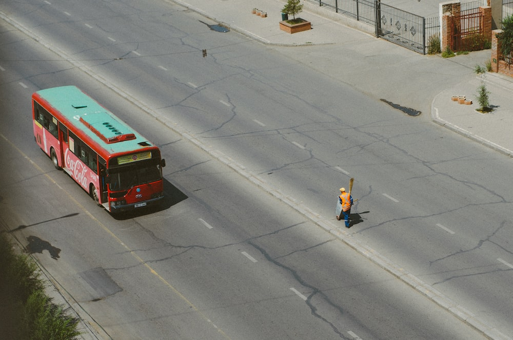birds eye view of man cleaning the road near bus