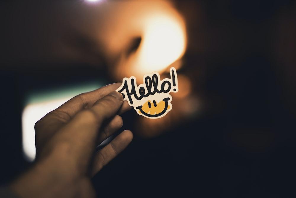 person holding Hello! sticker