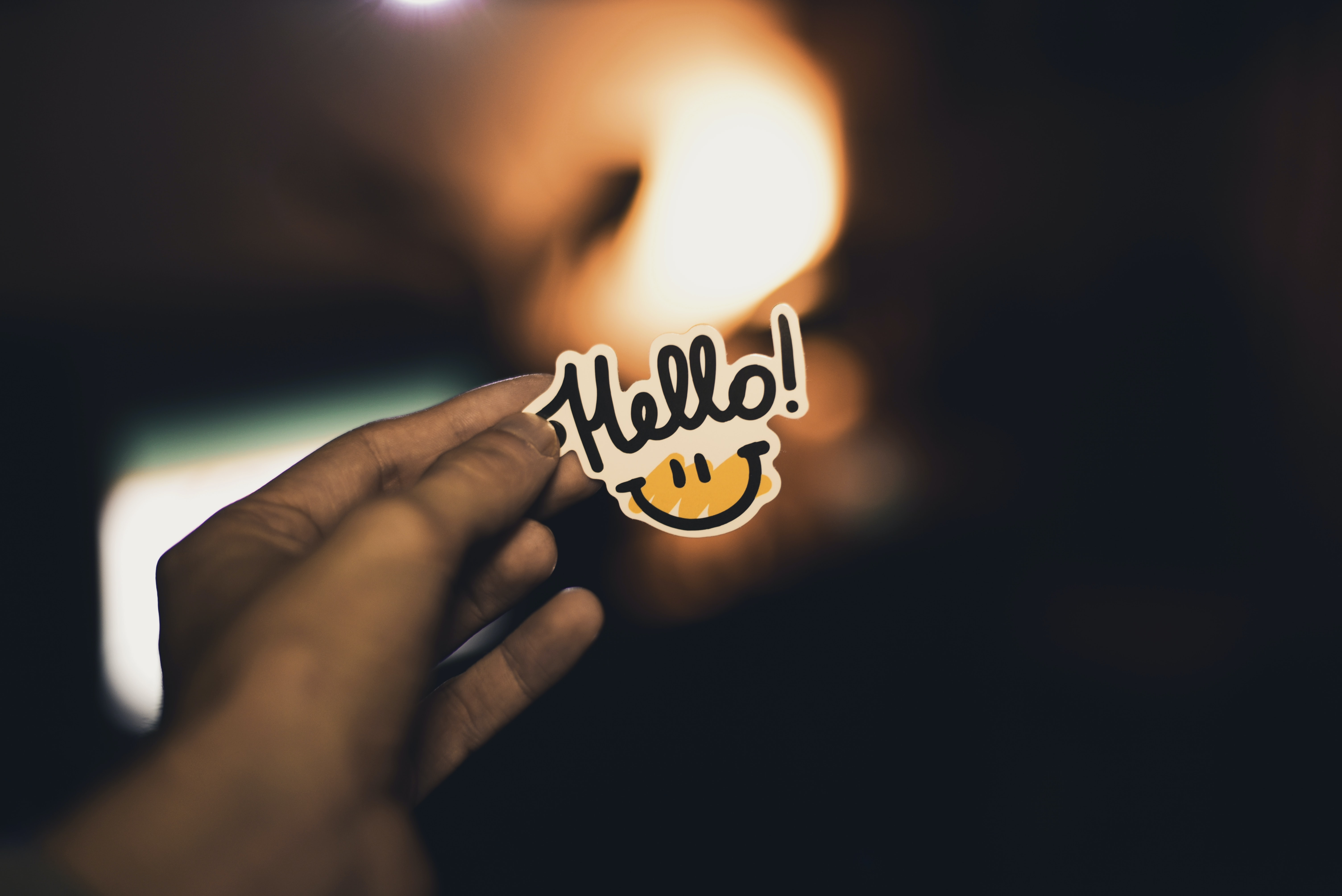 """Outstretched hands holding a sticker with a smiley face that says """"hello!"""""""
