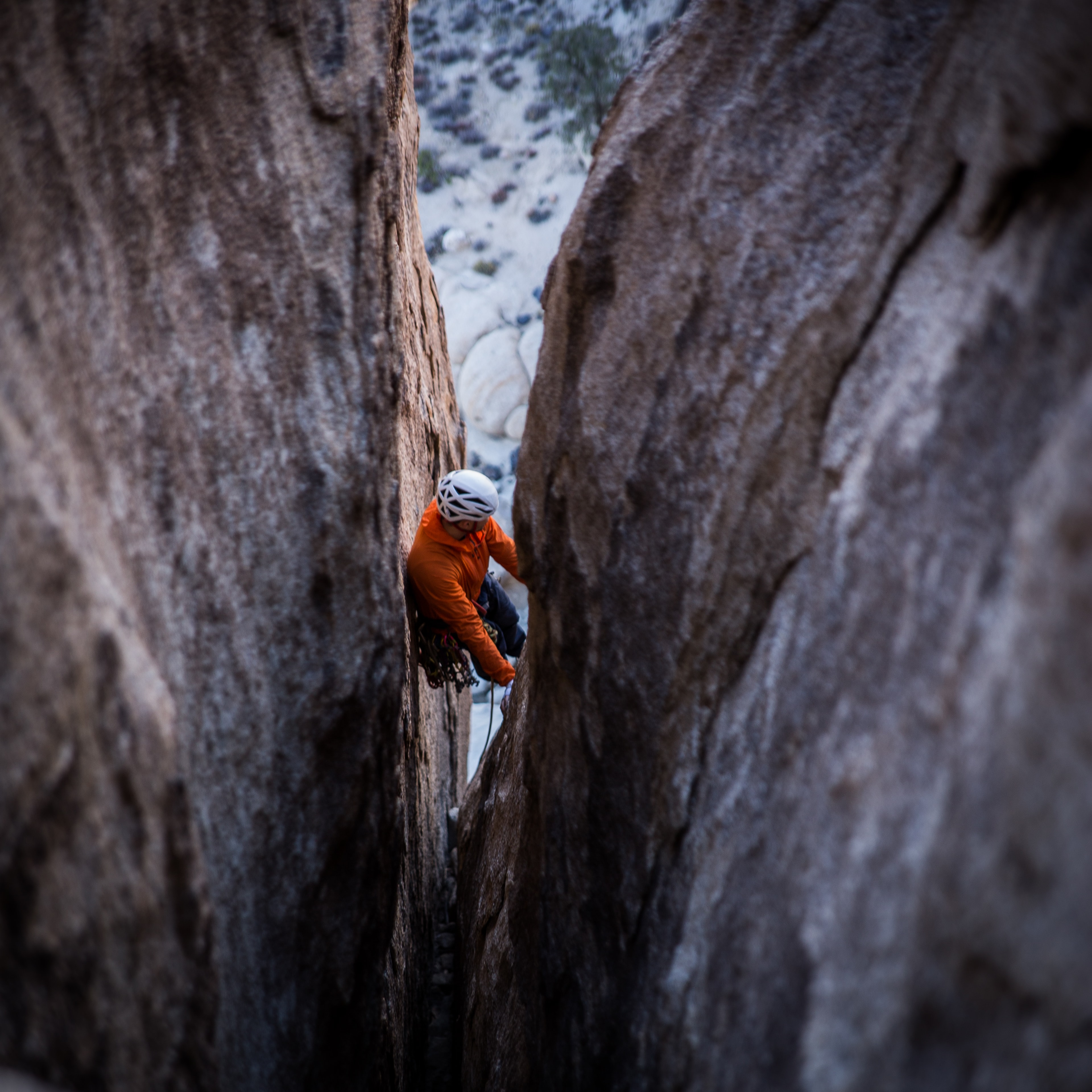 A person wearing an orange sweater and a white helmet rock climbing at Joshua Tree National Park Visitor Center