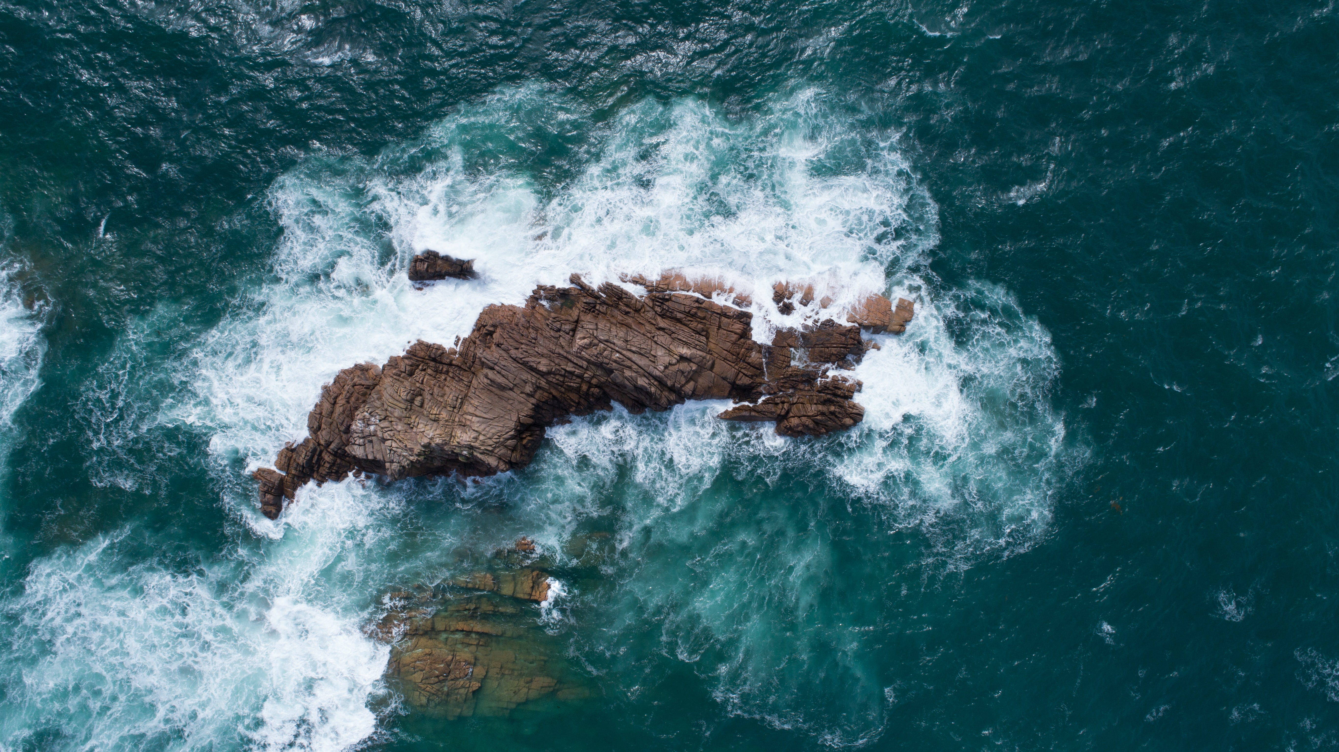 Drone view of the ocean waves crashing on the rock at Câtel, Guernsey