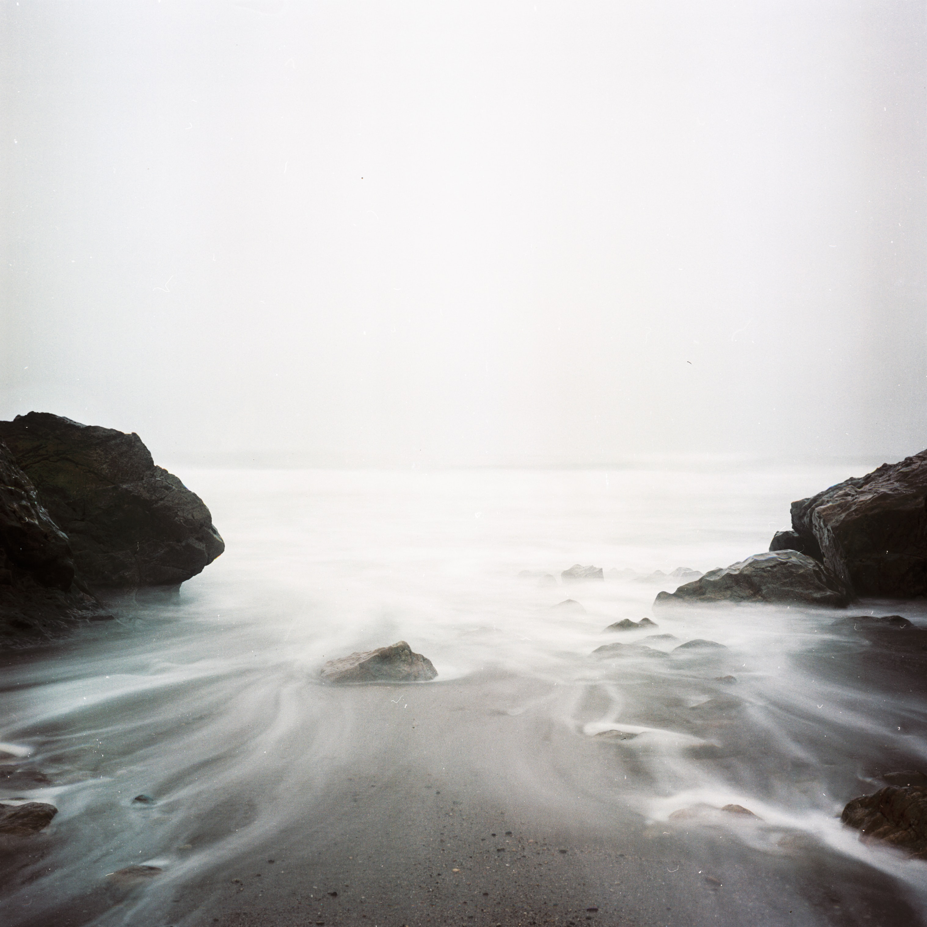 Long exposure photo of the ocean coming in the rocky bay