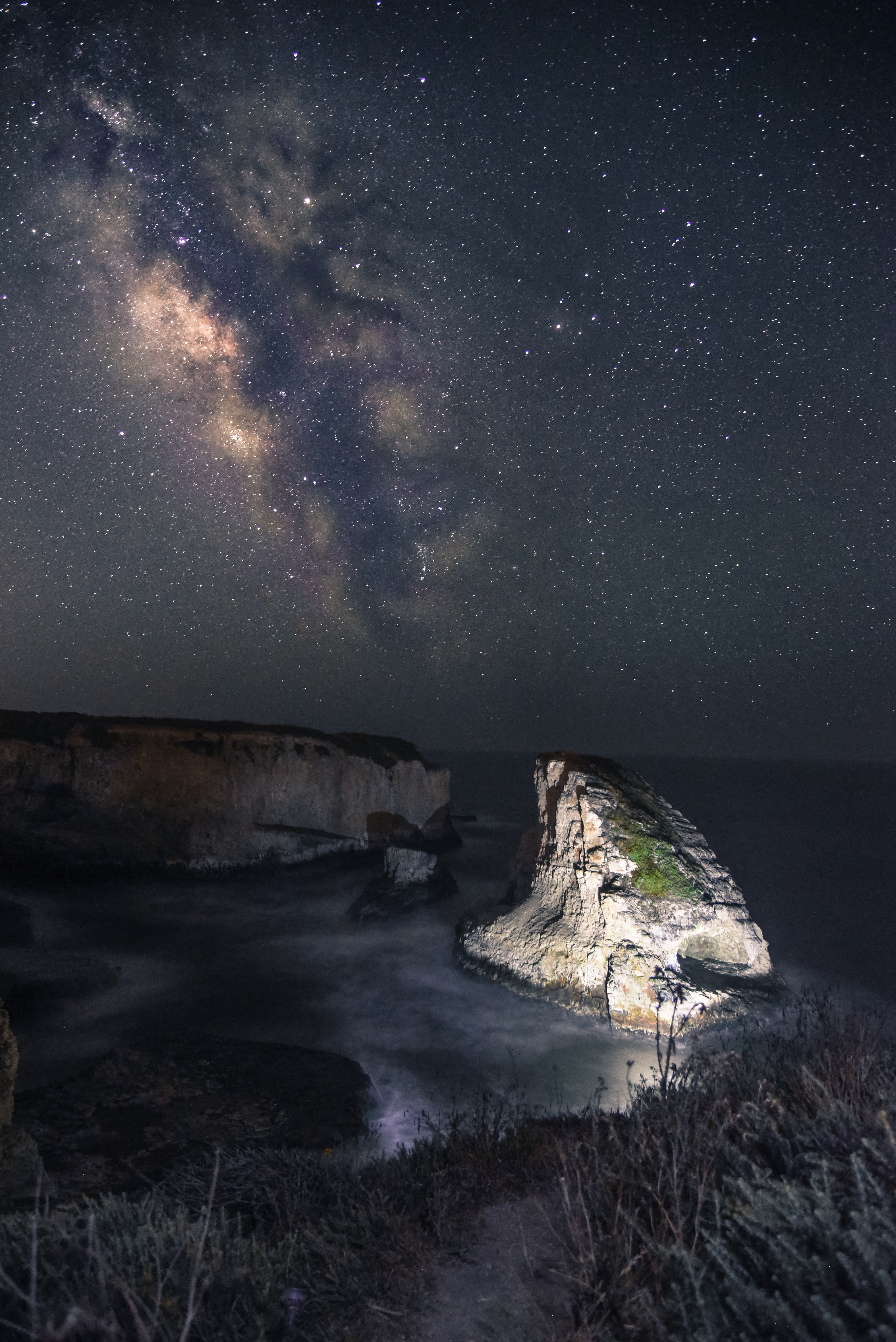 The Milky Way rises above the lighted up Shark Fin Cove in the star-studded night.
