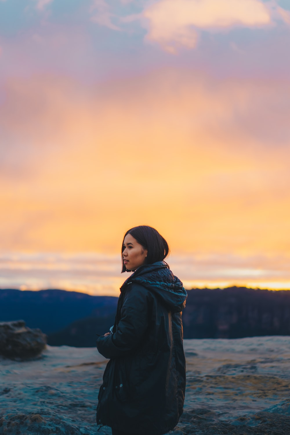 woman in black jacket standing on hill during daytime