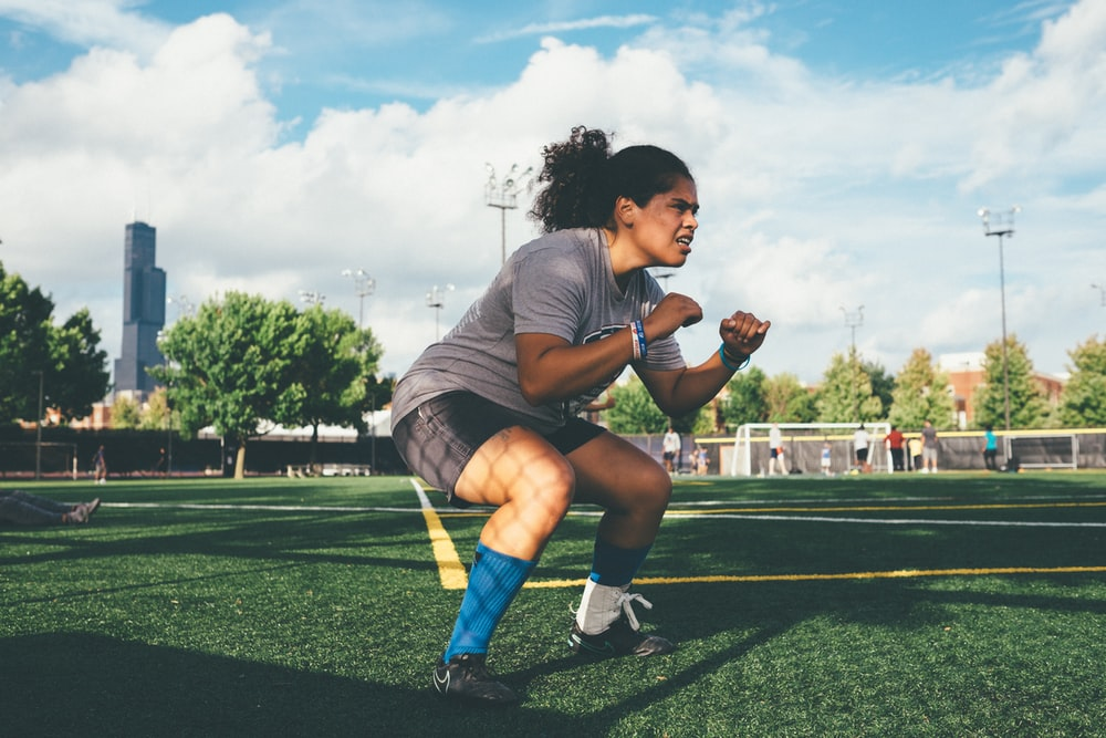Athletic woman in position to during soccer practice on a field