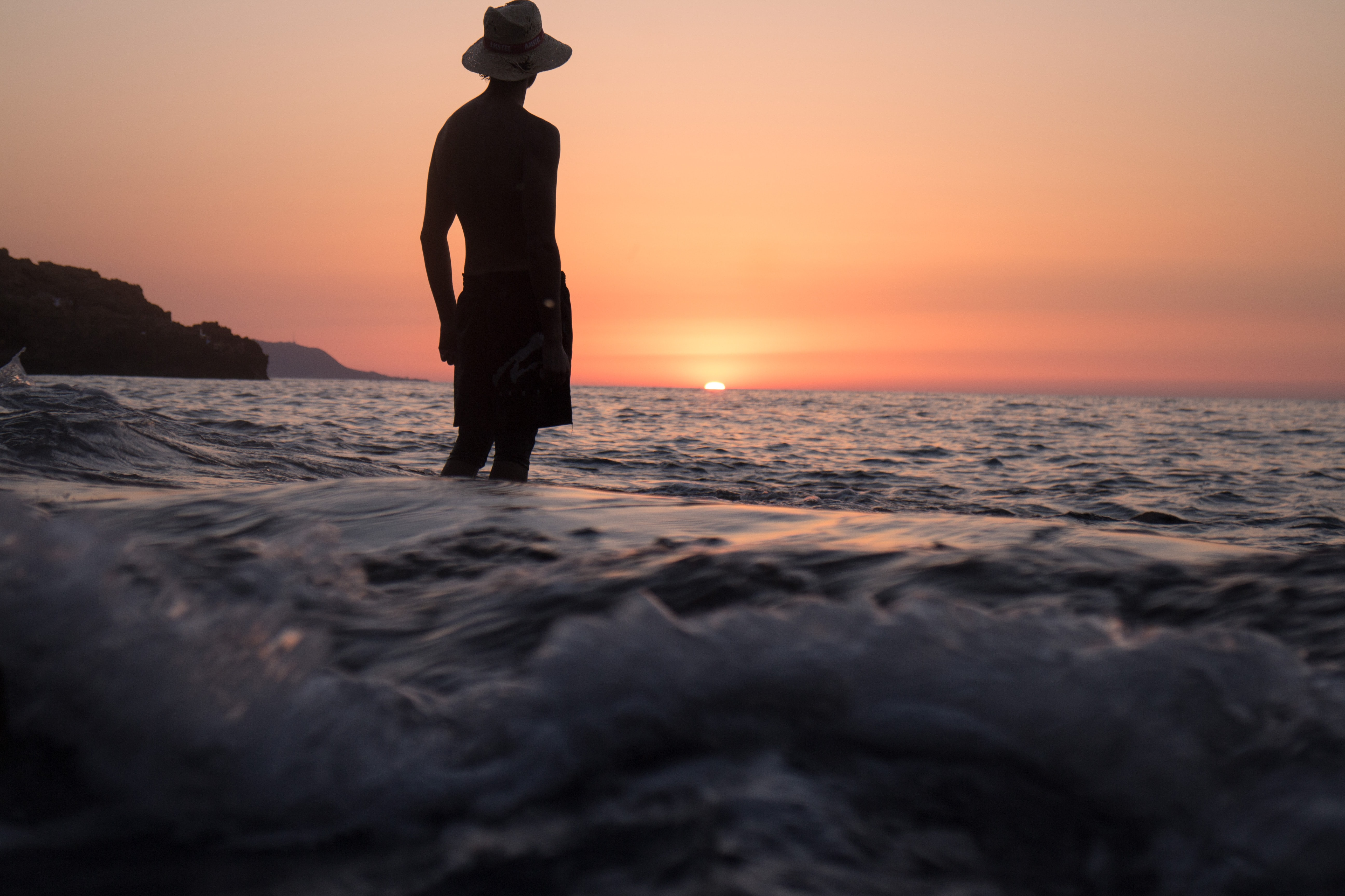 silhouette of person standing on shallow seashore facing sunset