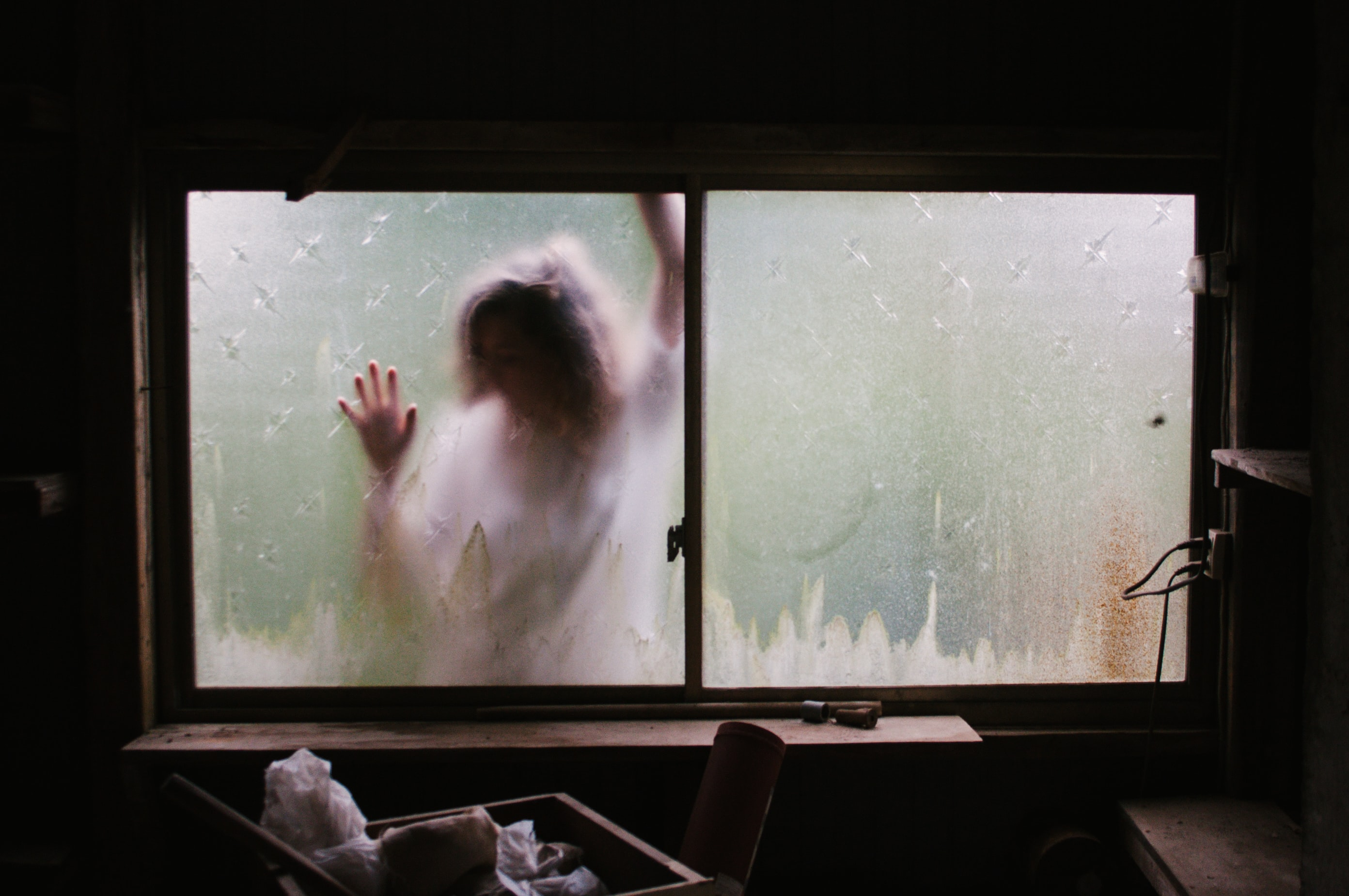 Scary woman wearing white trapped in a house with her hands on the glass.
