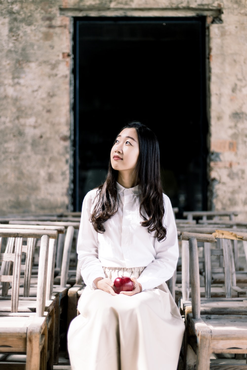woman in white button-up dress shirt and white pants holding apple sitting on chair