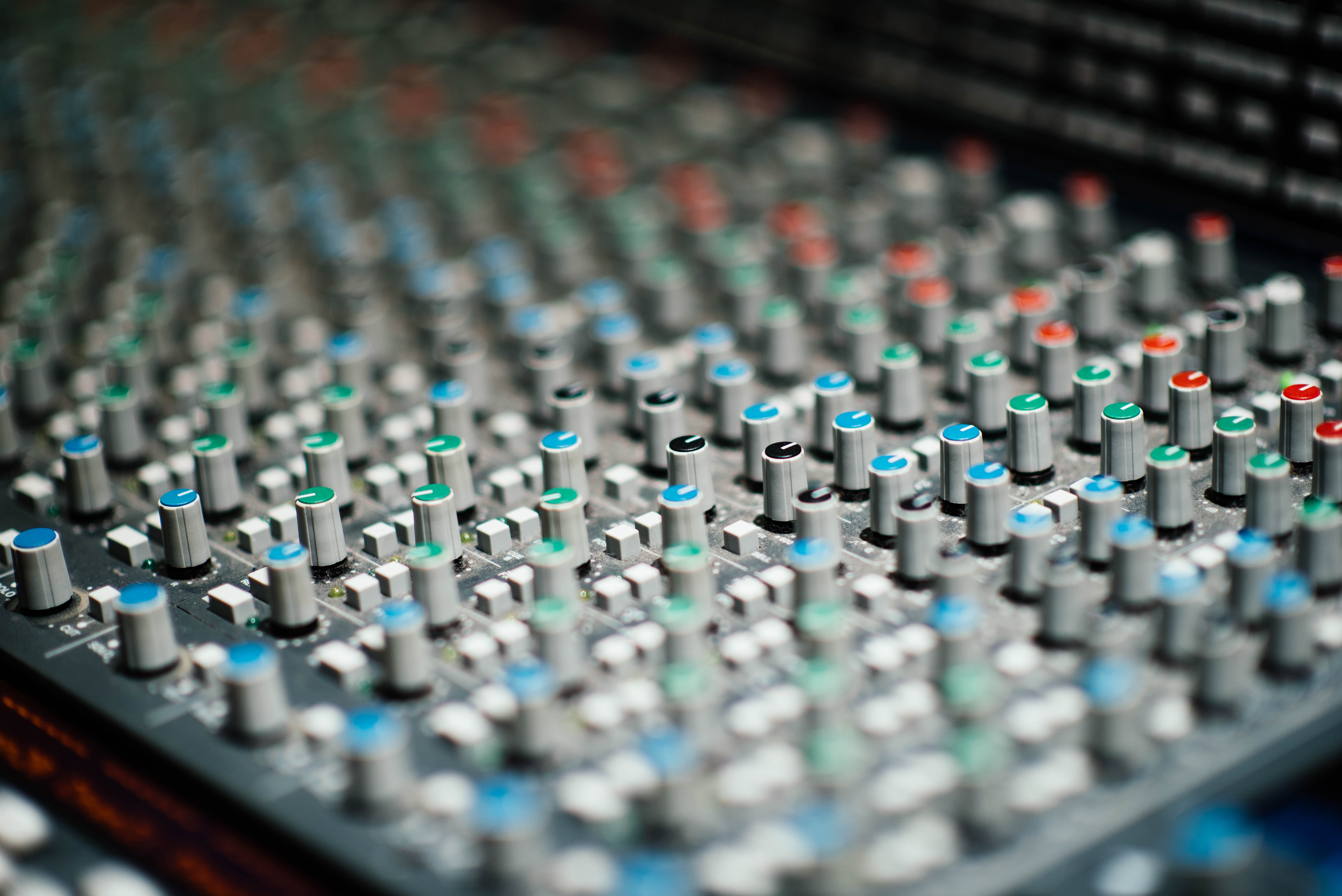 Macro of sound equipment mixing board with equalizers, knobs, and buttons
