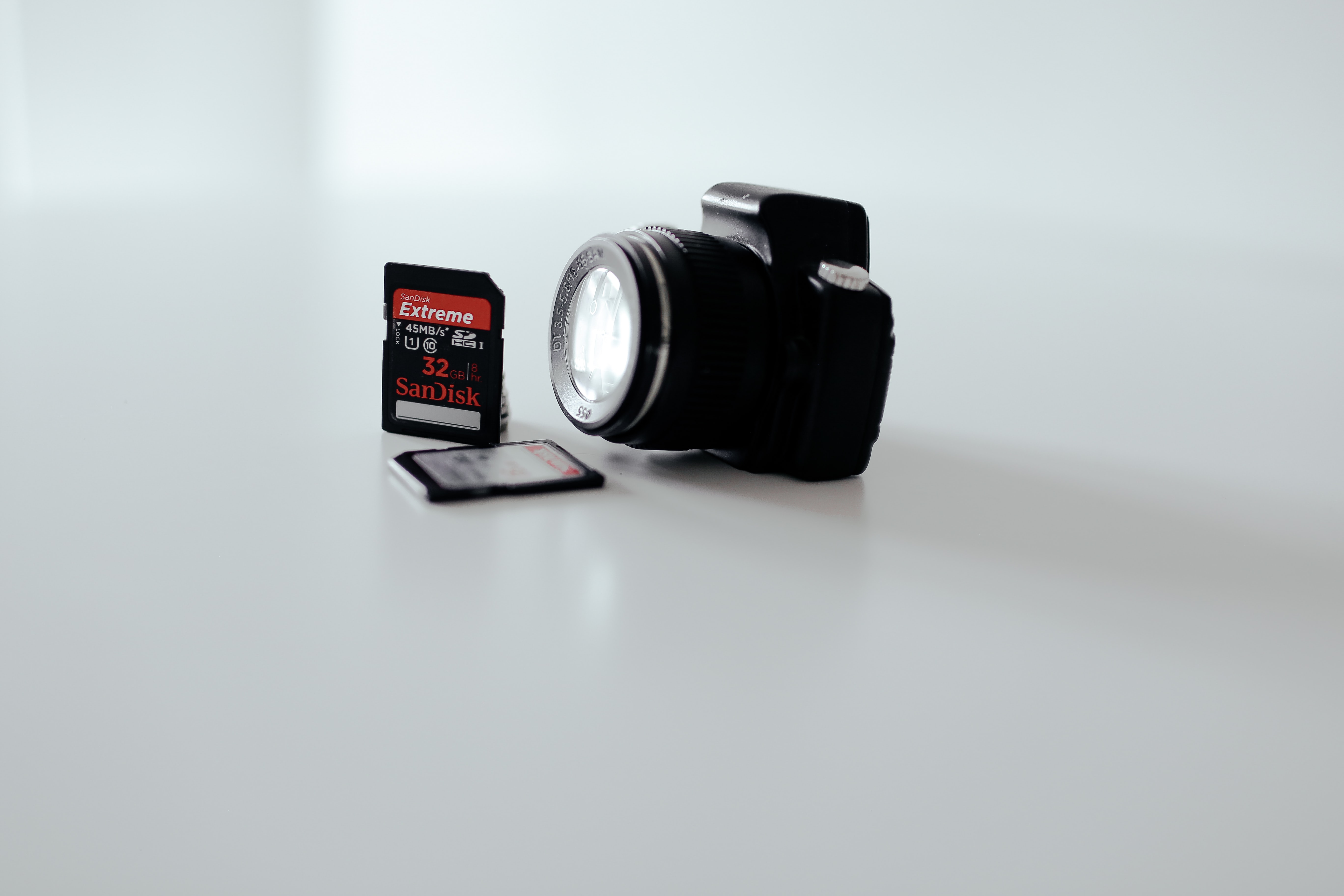 A minimalist photo of a camera lens and two SD memory cards