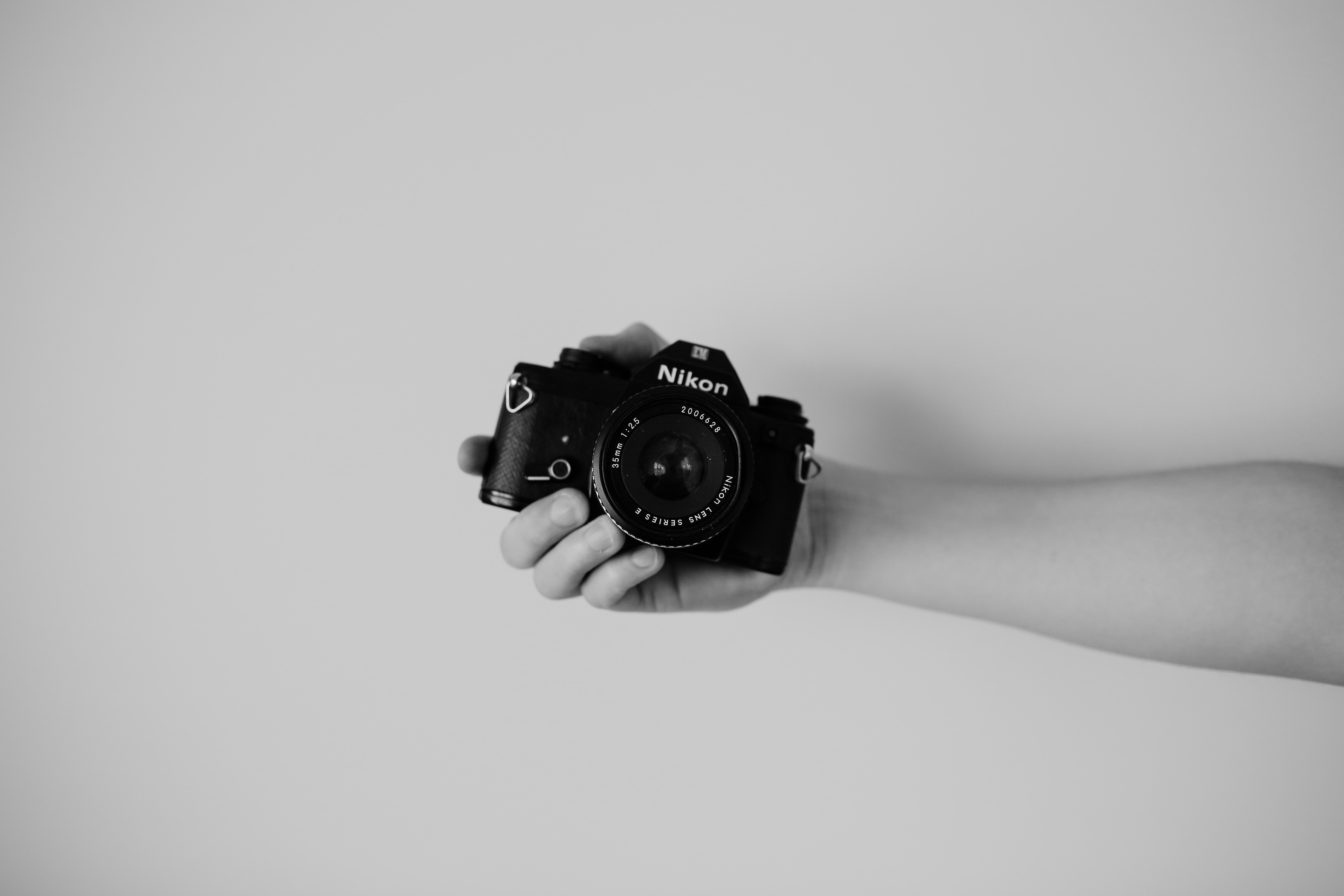 A black-and-white shot of a person holding a Nikon camera in their hand