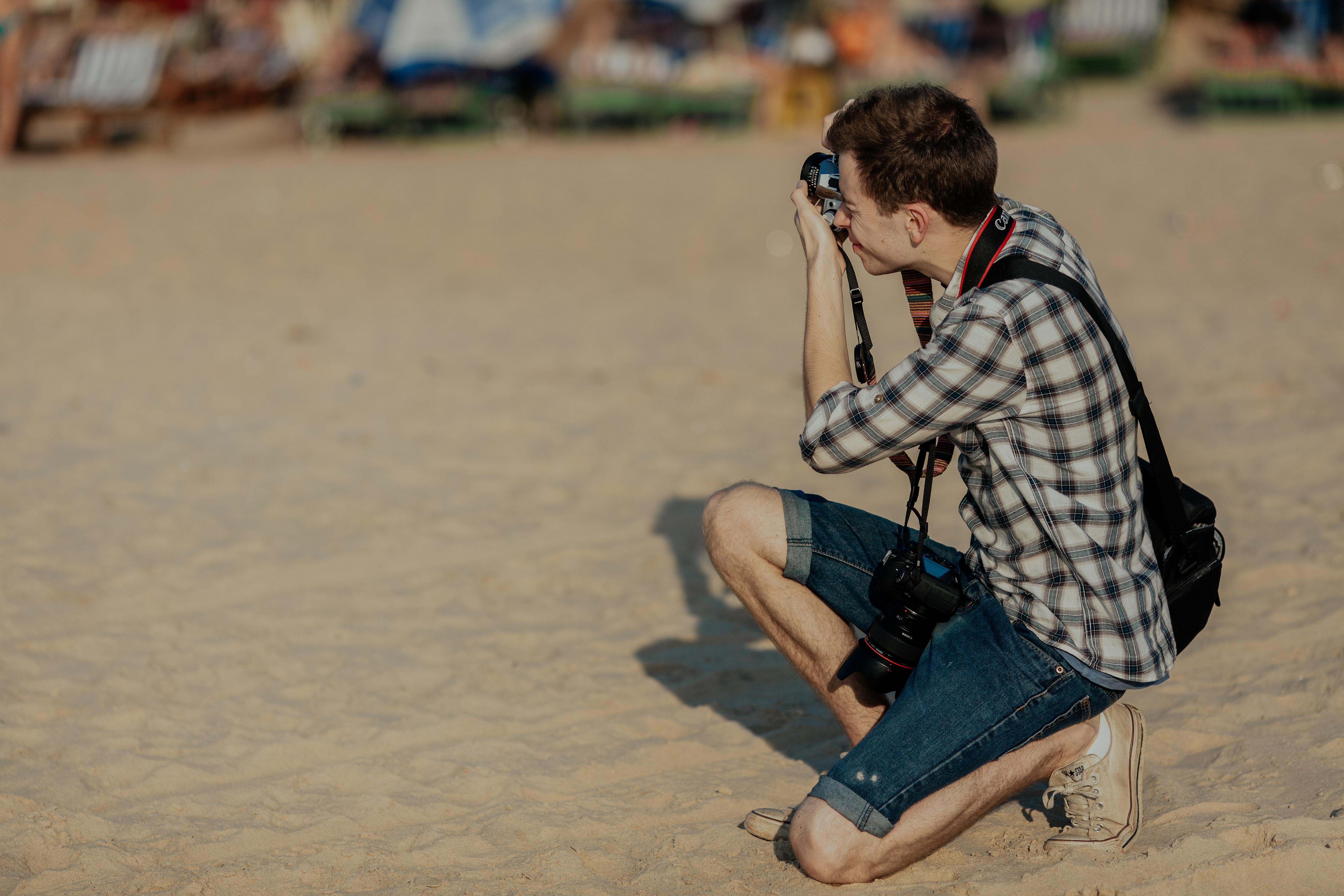 man kneeling taking photo