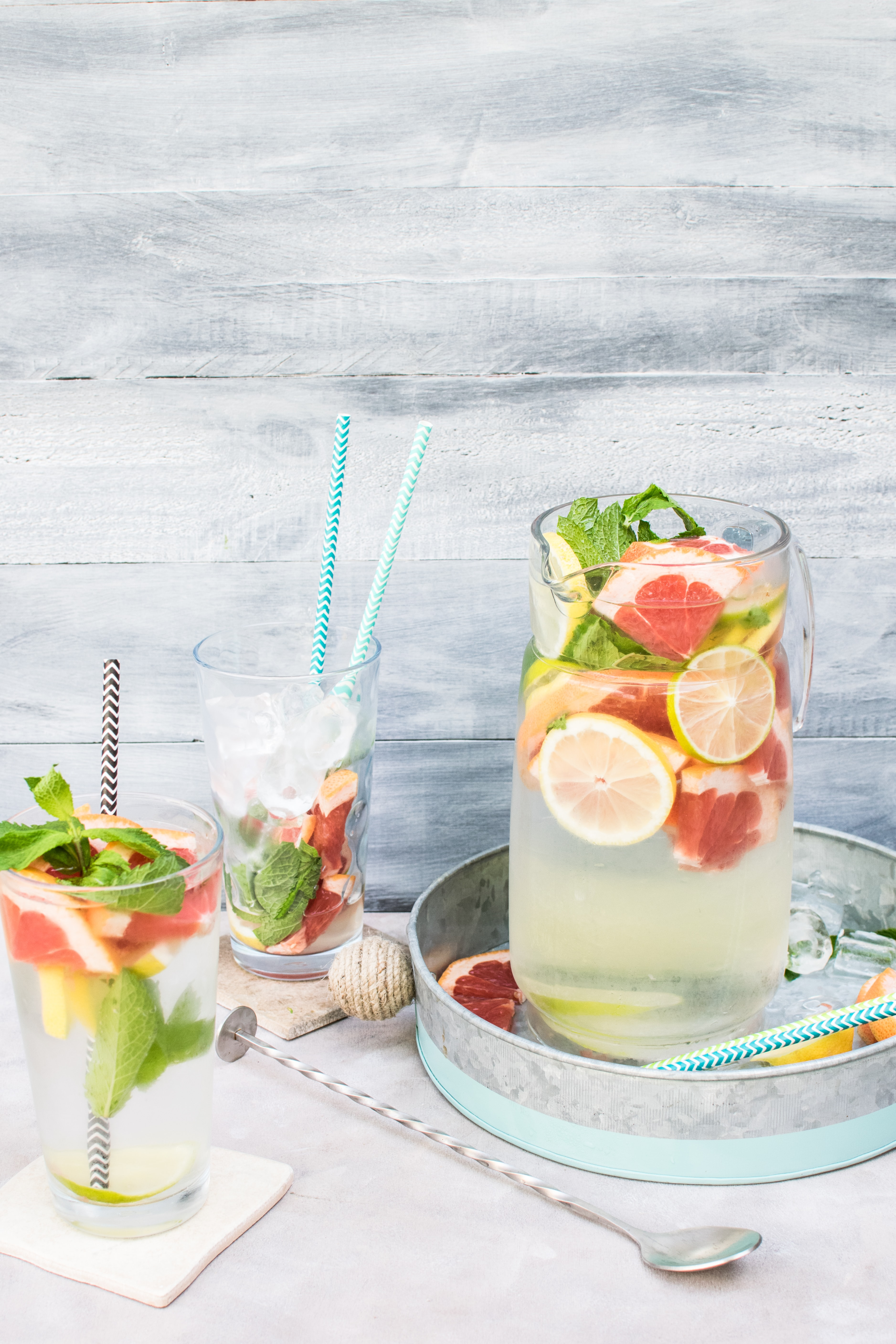 A cocktail table with a pitcher and two glasses filled with ice, lemons, grapefruits, mint, and more