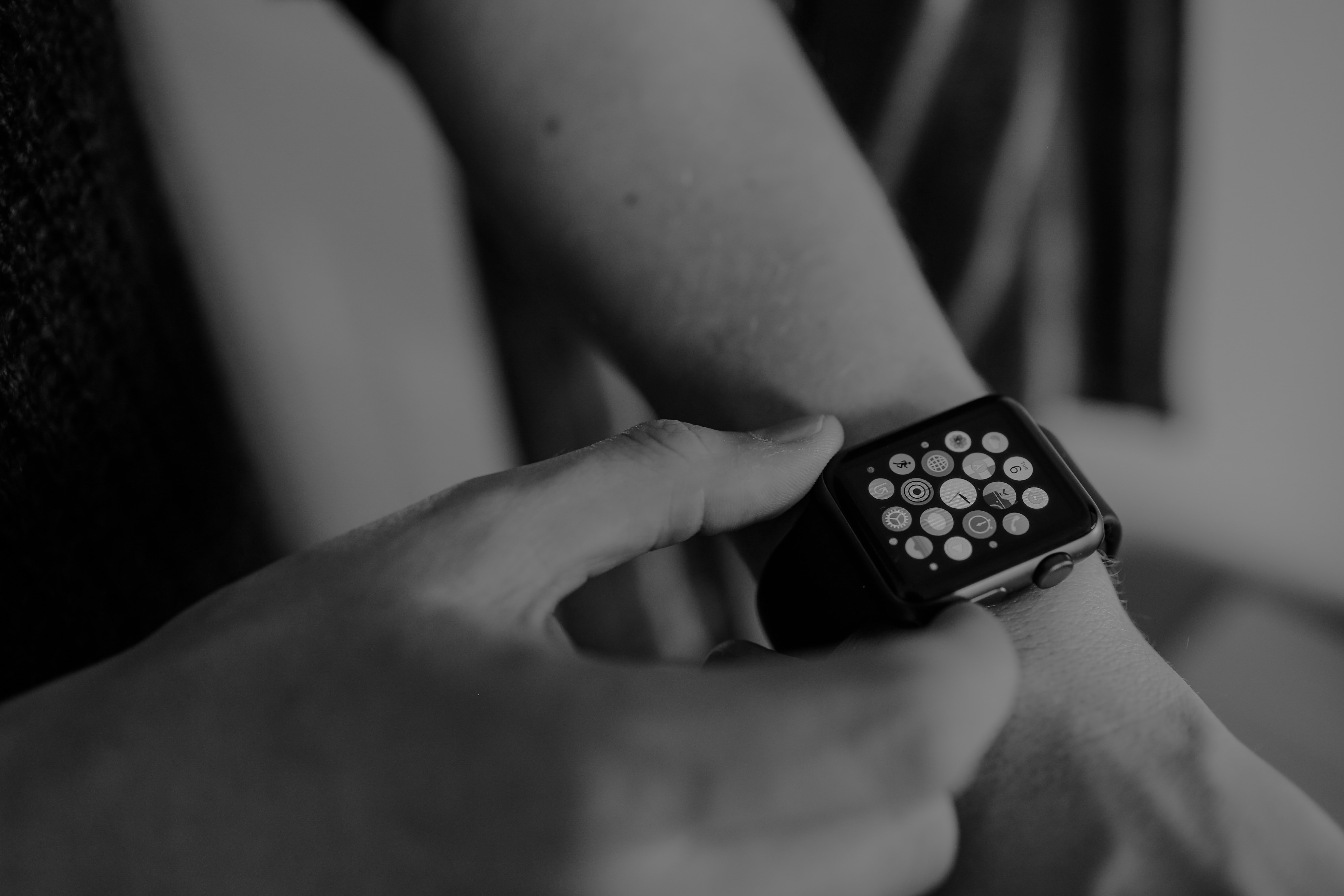Black and white photo of a person checking their Apple Watch