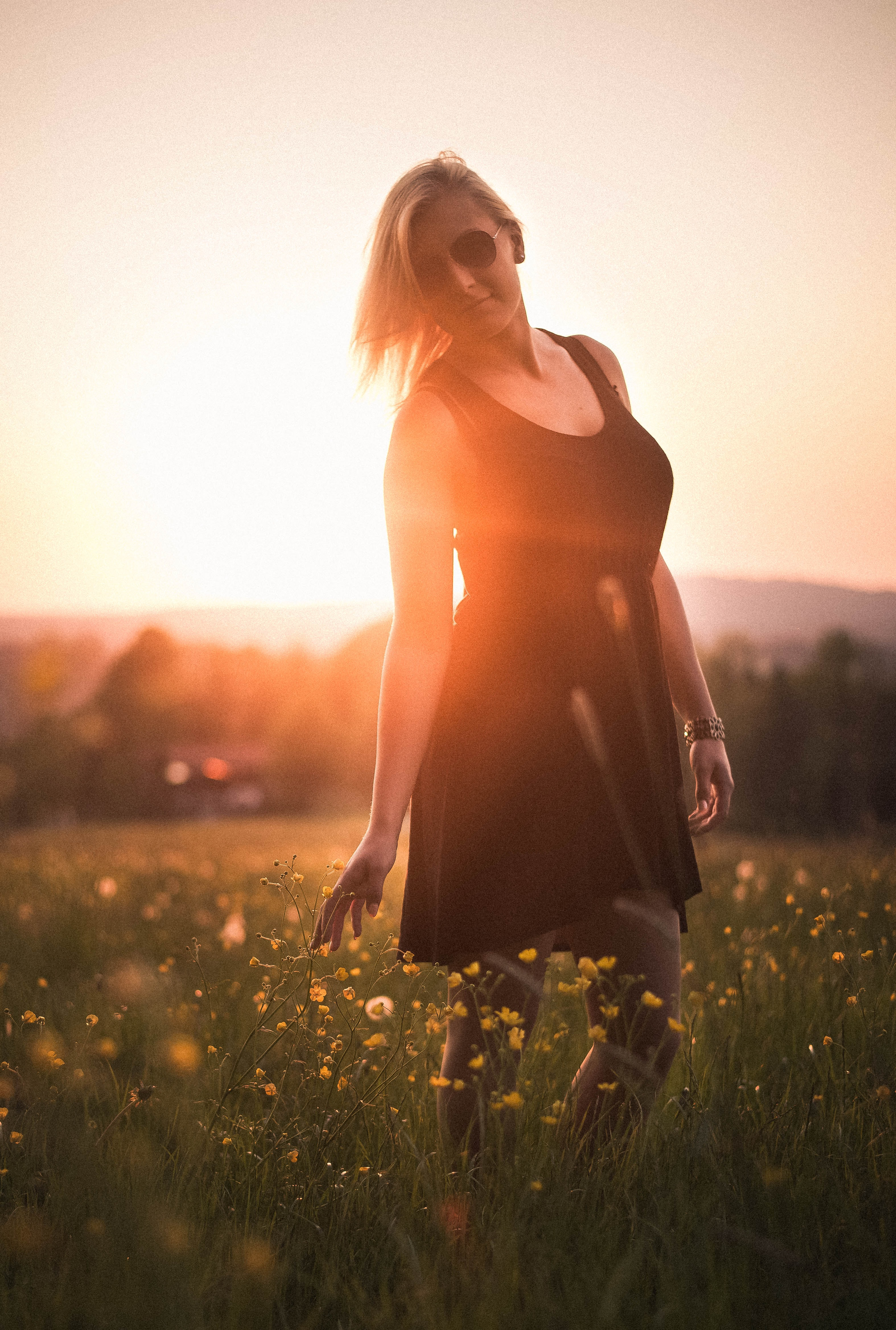 woman wearing black scoop-neck mini dress surrounded by flowers during sunset