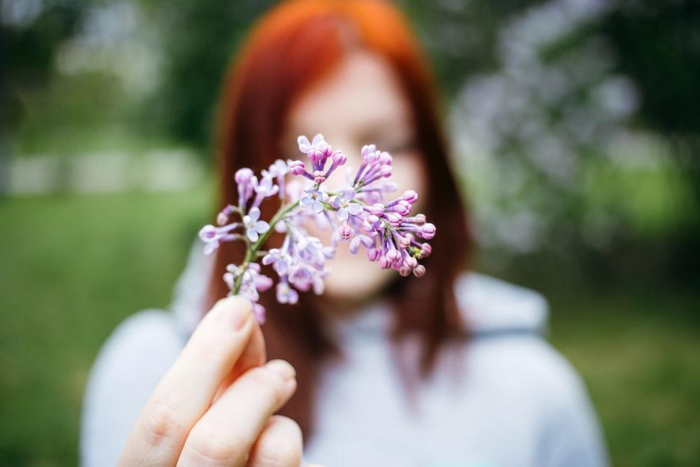 macro shot photo of woman holding purple flower standing outside