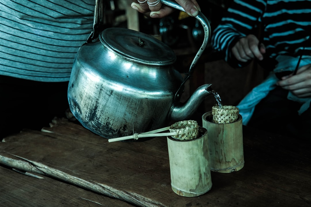 Metal teapot and wooden cups