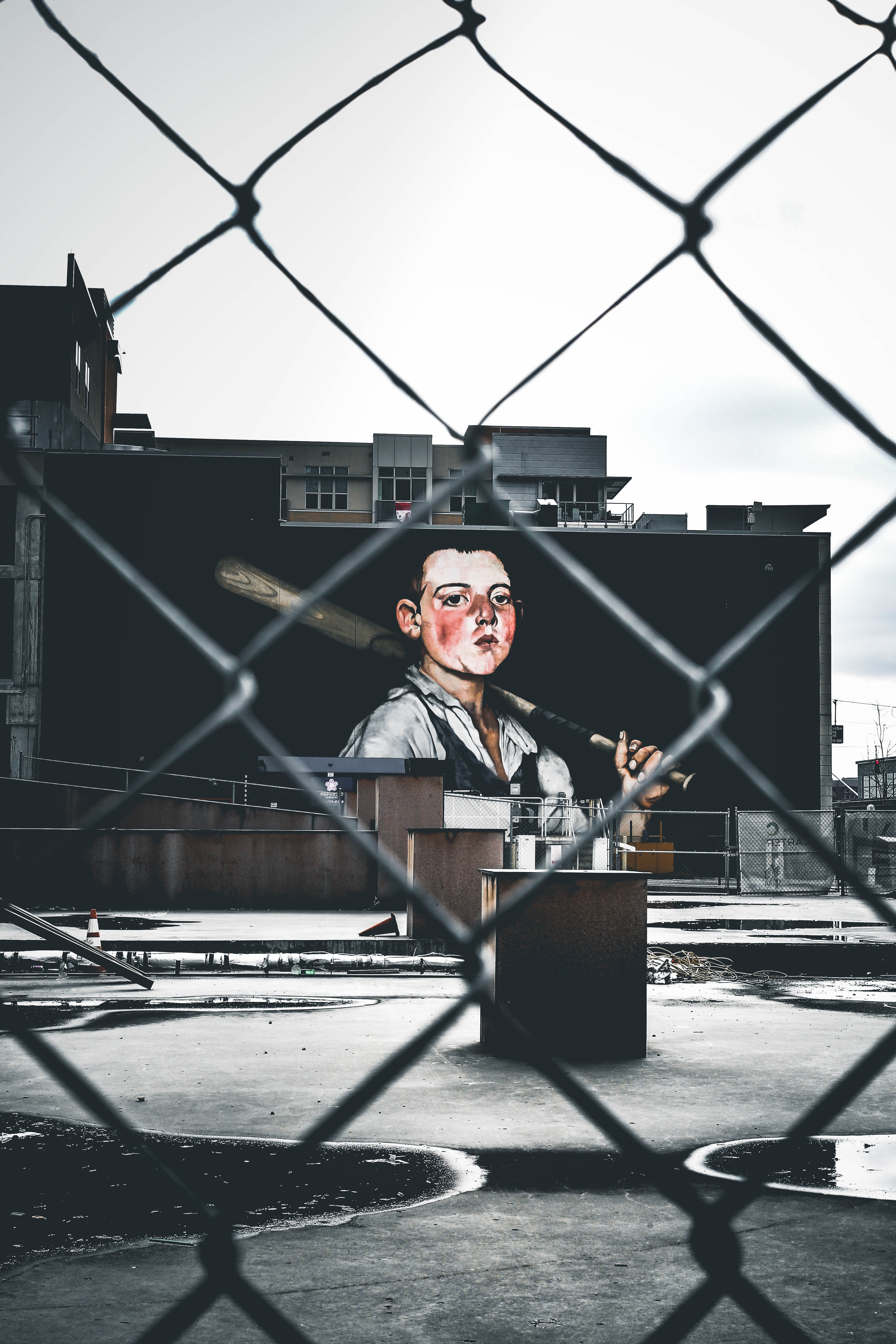 The view of art of man with baseball bat from a chain fence of an urban building