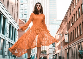 woman in orange long-sleeved dress between buildings during daytime