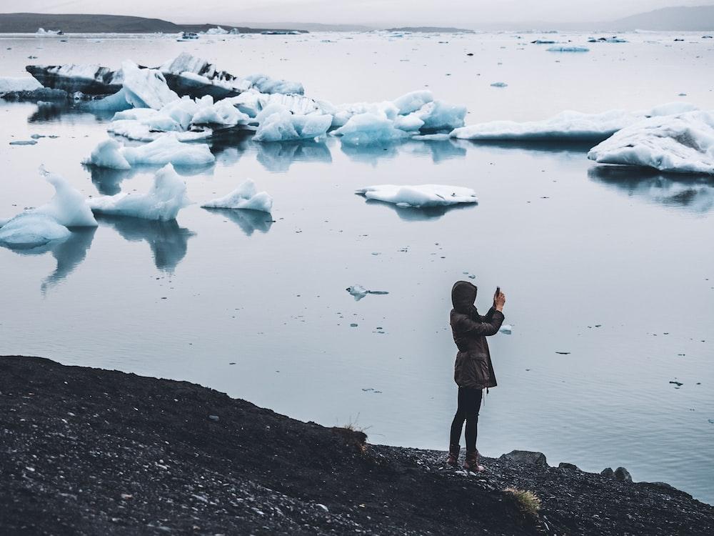 woman taking photo standing near body of water